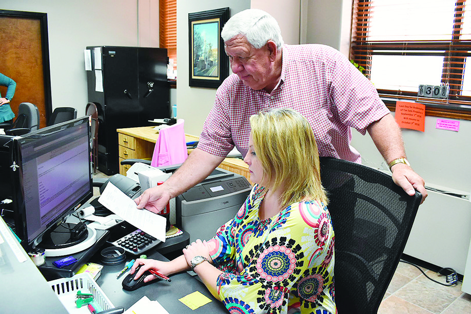 Walker County Revenue Commissioner Jerry Guthrie, standing, goes over some details with Deputy Collector Amanda Butler on Thursday. Guthrie and officials in the office had to deal with two potential scams that they were made aware of that day.