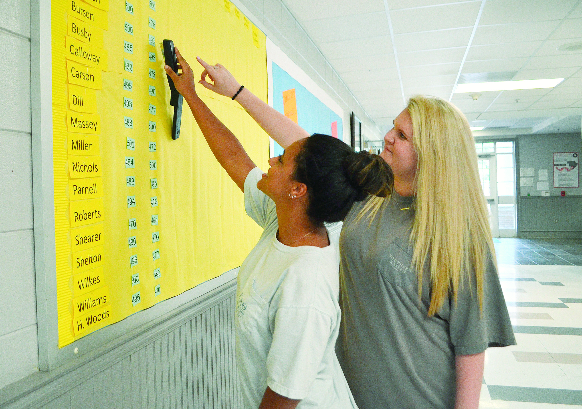 From left to right, Oakman High School seniors Samantha Homan and Lani Herron work on a board that is used to track student attendance.