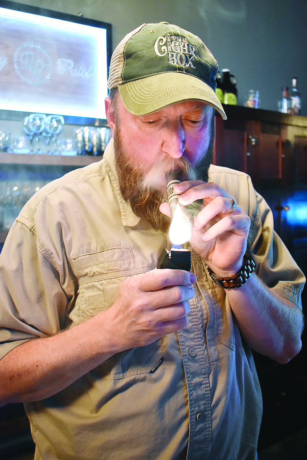 Shawn Doss, the owner of The Cigar Box, lights up a cigar on Tuesday before a ribbon-cutting ceremony for the cigar store and cigar lounge.