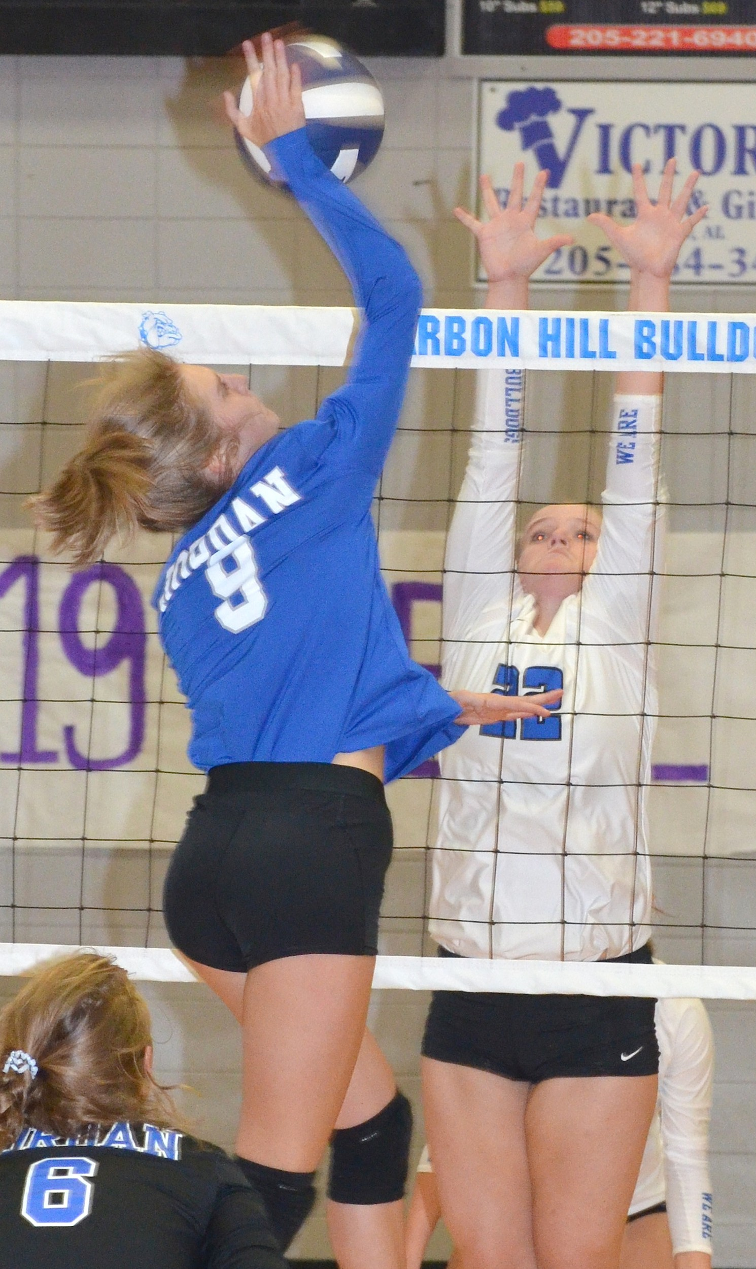 Mortimer Jordan's Madeline Snow (9) looks to hit past the block of Carbon Hill's Lacey Evans (22) during their match at Carbon Hill High School on Tuesday. The top-ranked Bulldogs dropped the first set, but bounced back for a 20-25, 25-17, 25-13, 25-17 win.