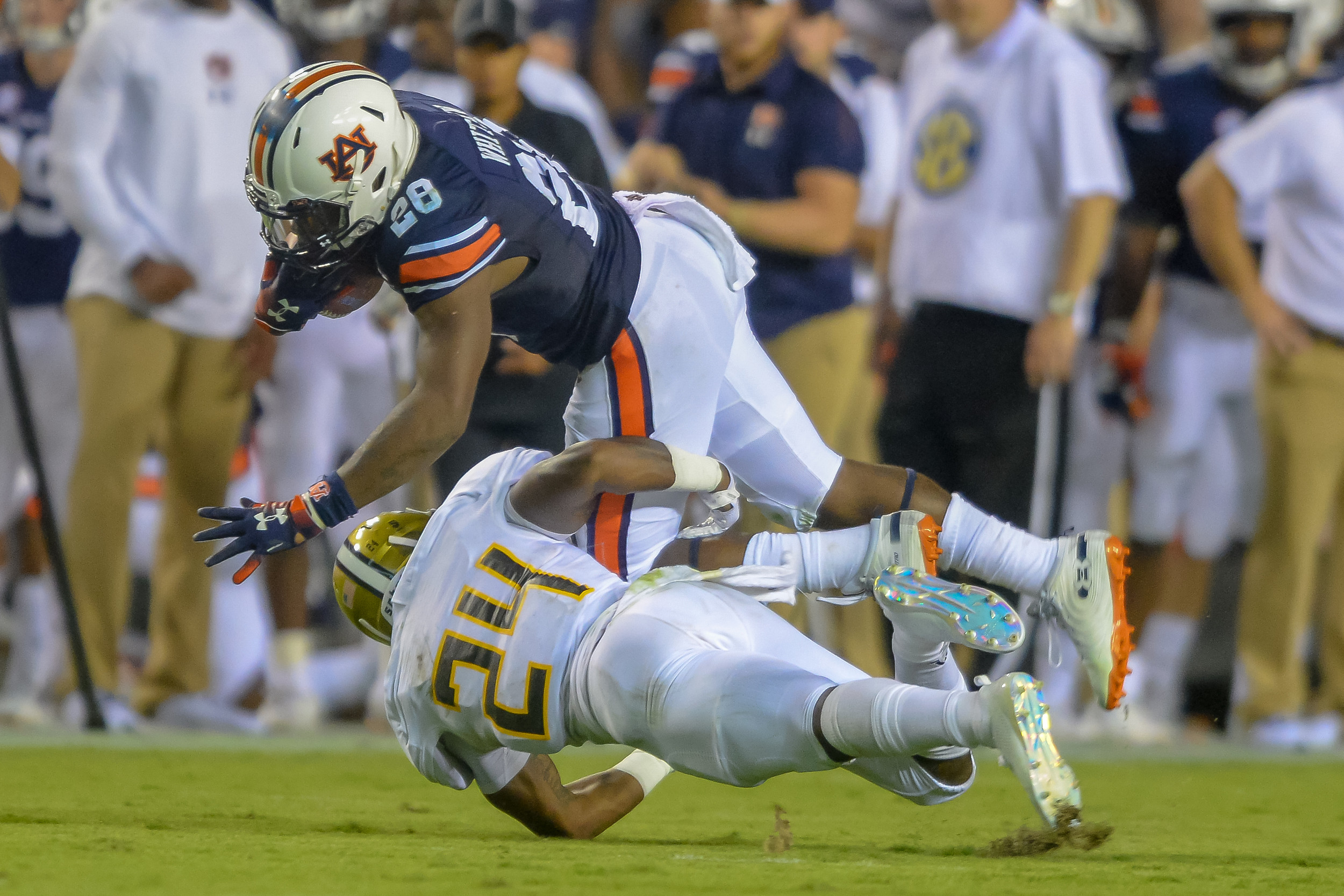 Auburn Tigers running back JaTarvious Whitlow (28) runs though the tackle of Alabama State Hornets defensive back Joshua Hill (24) during the first half of Saturday's game, at Jordan Hare Stadium in Auburn, AL. (Contributed by Jeff Johnsey)