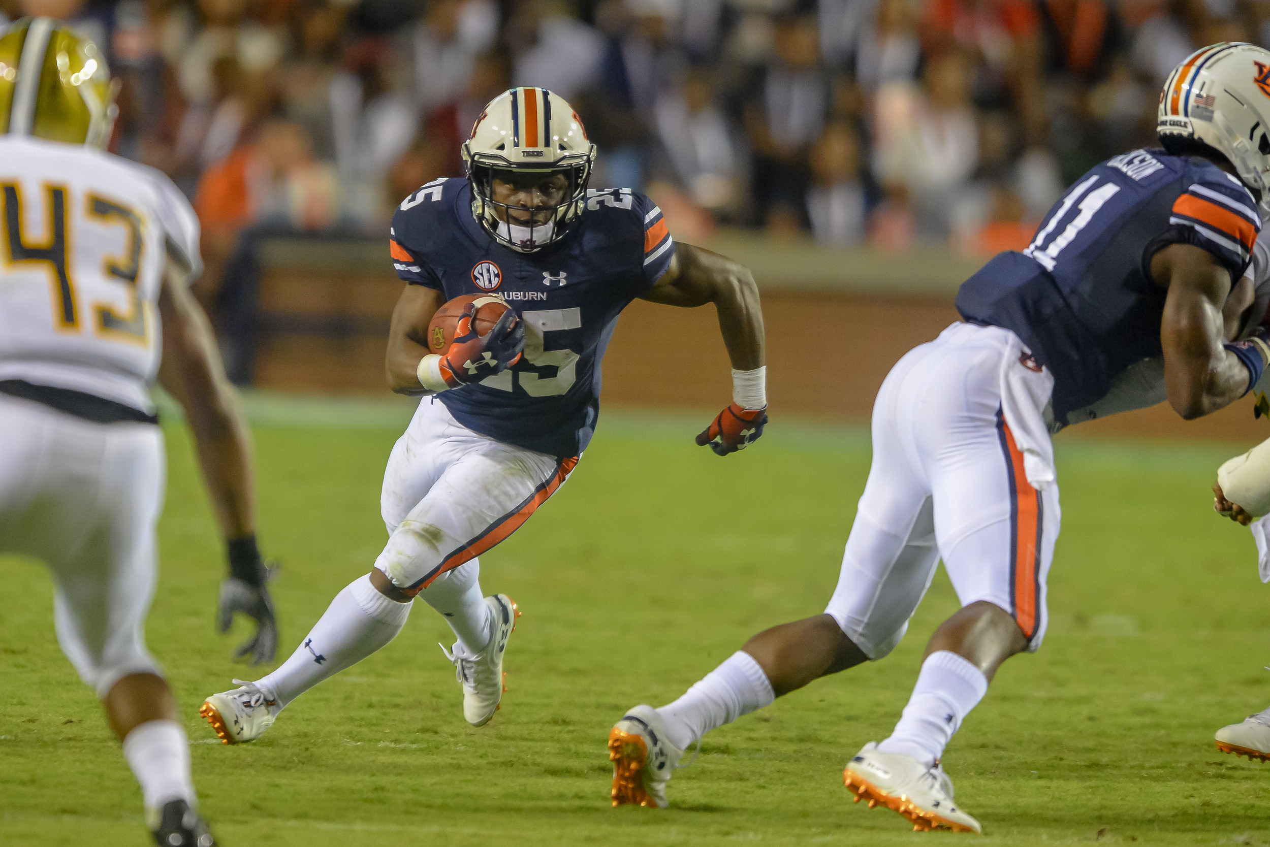 Auburn Tigers running back Shaun Shivers (25) runs behind the block of wide receiver Shedrick Jackson (11) during the second half of Saturday's game, at Jordan Hare Stadium in Auburn Atlanta. (Contributed by Jeff Johnsey)