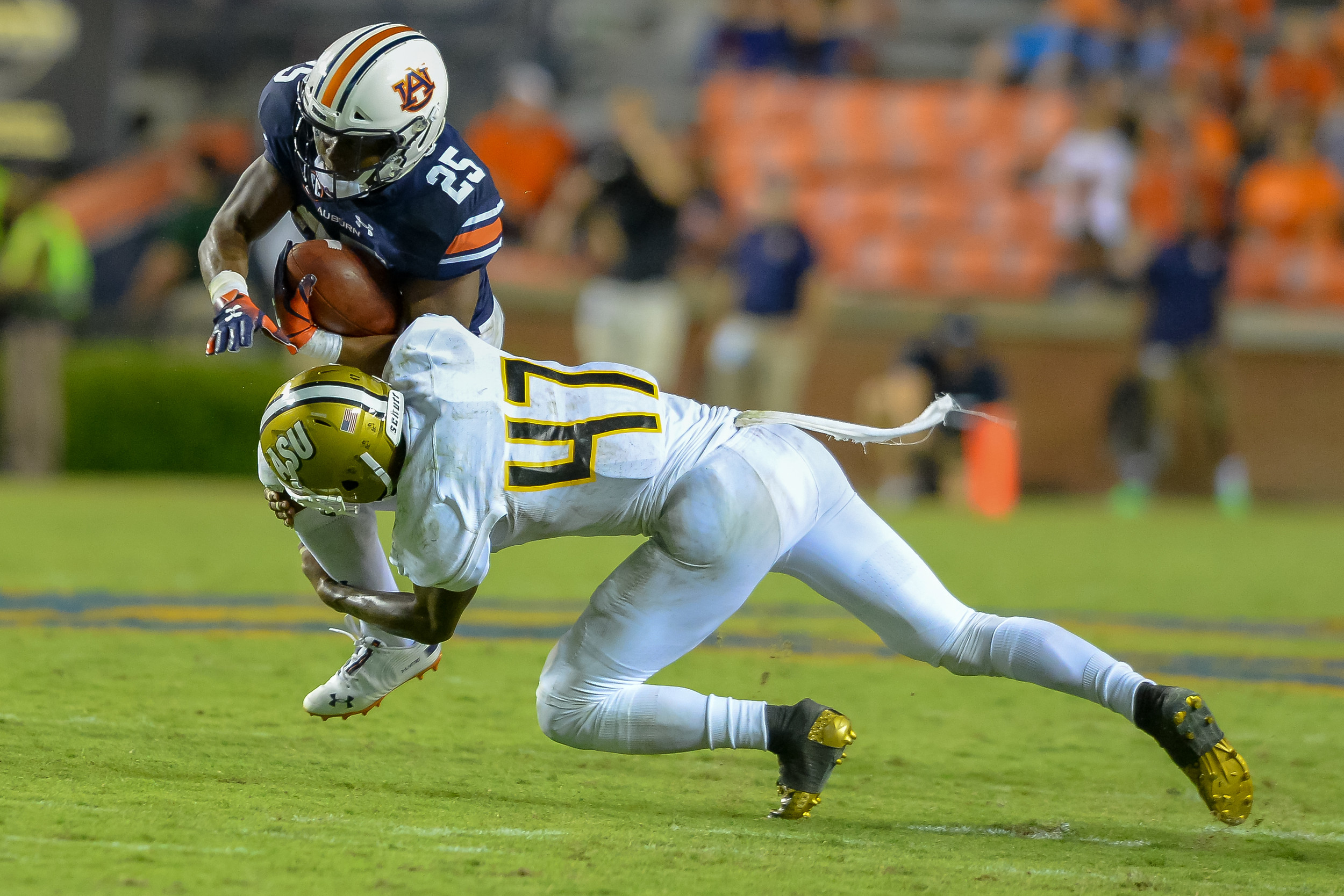 Auburn Tigers running back Shaun Shivers (25) is upended by Alabama State Hornets defensive back Kurron Ramsey (47) during the second half of Saturday's game, at Jordan Hare Stadium in Auburn Atlanta. (Contributed by Jeff Johnsey)
