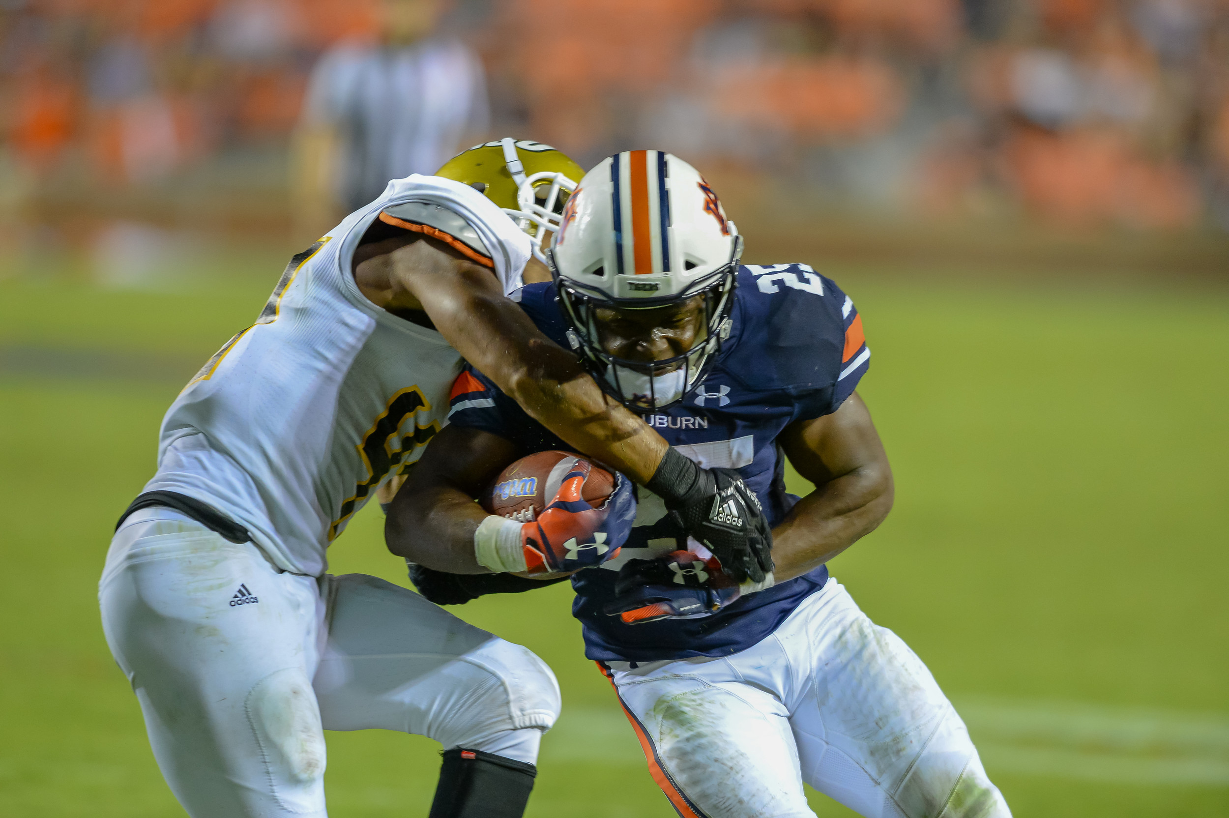 Auburn Tigers running back Shaun Shivers (25) is tackled by Alabama State Hornets defensive back Kurron Ramsey (47) during the second half of Saturday's game, at Jordan Hare Stadium in Auburn Atlanta. (Contributed by Jeff Johnsey)