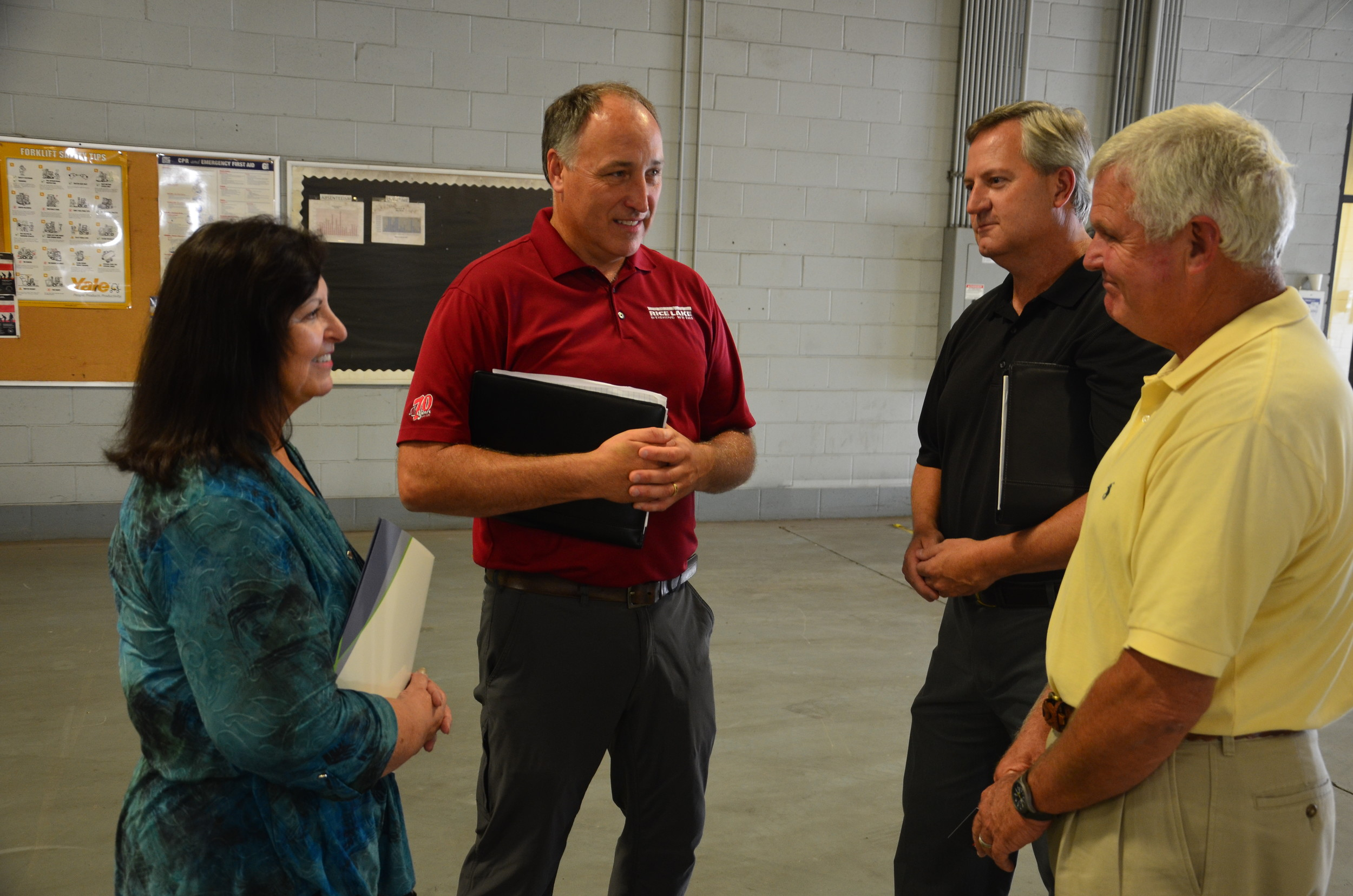 Rice Lake Vice President of Manufacturing Dominic Hodkiewicz and Marian Powell, general manager, speak with Mayor David O'Mary and David Knight, director of the Walker County Development Authority and Jasper Industrial Development Board at the new Rice Lake manufacturing facility in Jasper.