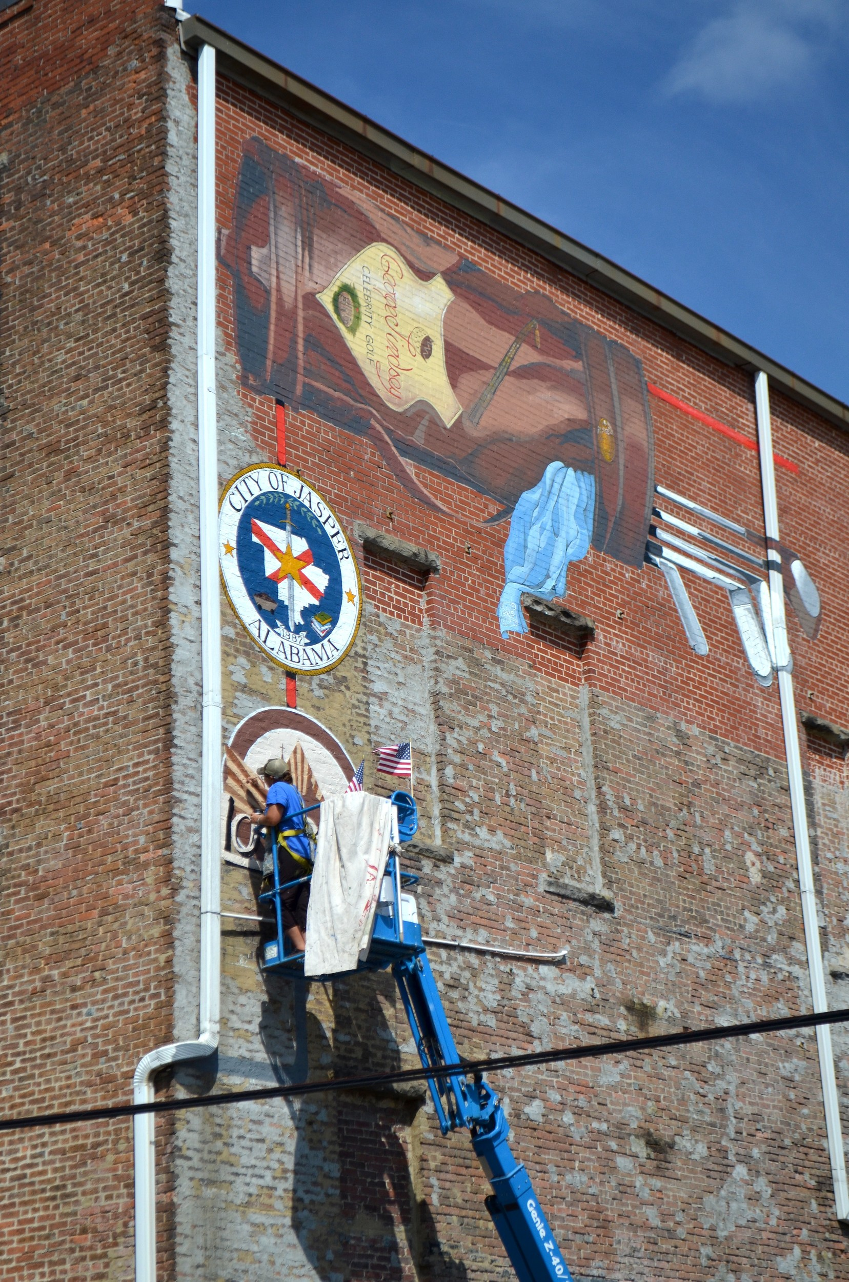 Artist Missy Miles put the finishing touches on a mural along 19th Street in downtown Jasper Wednesday that pays tribute to Burton Manufacturing Co., a business that used to be located in Jasper to produce golf bags and other items. It is her tallest mural to date and her fourth in Jasper.