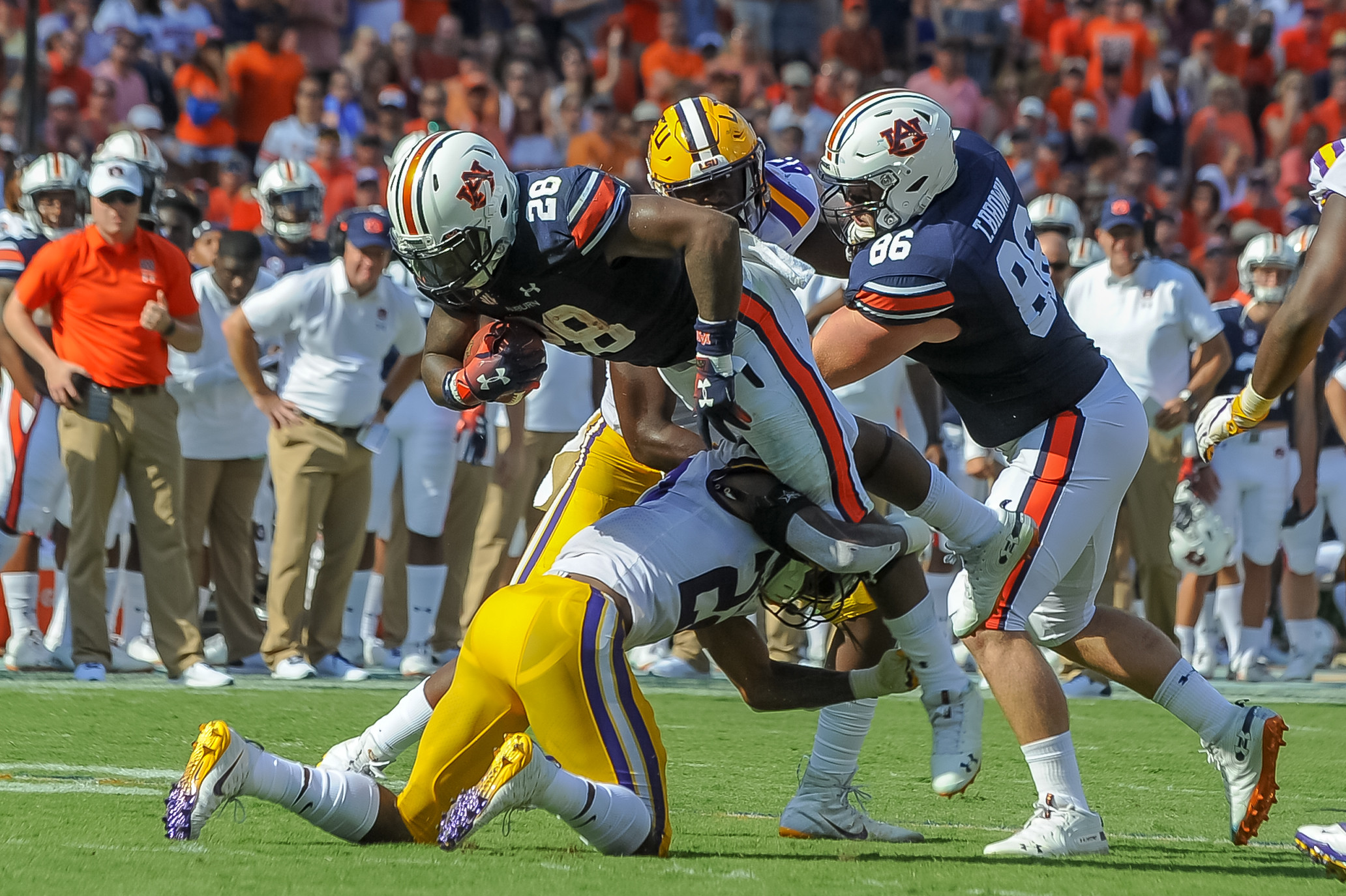 Auburn Tigers running back JaTarvious Whitlow (28) is upended by LSU Tigers cornerback Kristian Fulton (22) during the first half of Saturday's game, at Jordan Hare Stadium in Auburn. (Contributed by Jeff Johnsey)