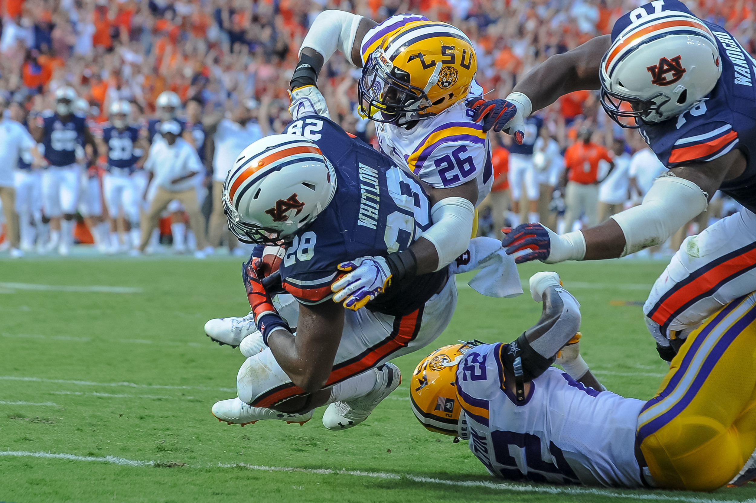 Auburn Tigers running back JaTarvious Whitlow (28) scores as LSU Tigers safety John Battle (26) tries to tackle during the first half of Saturday's game, at Jordan Hare Stadium in Auburn. (Contributed by Jeff Johnsey)