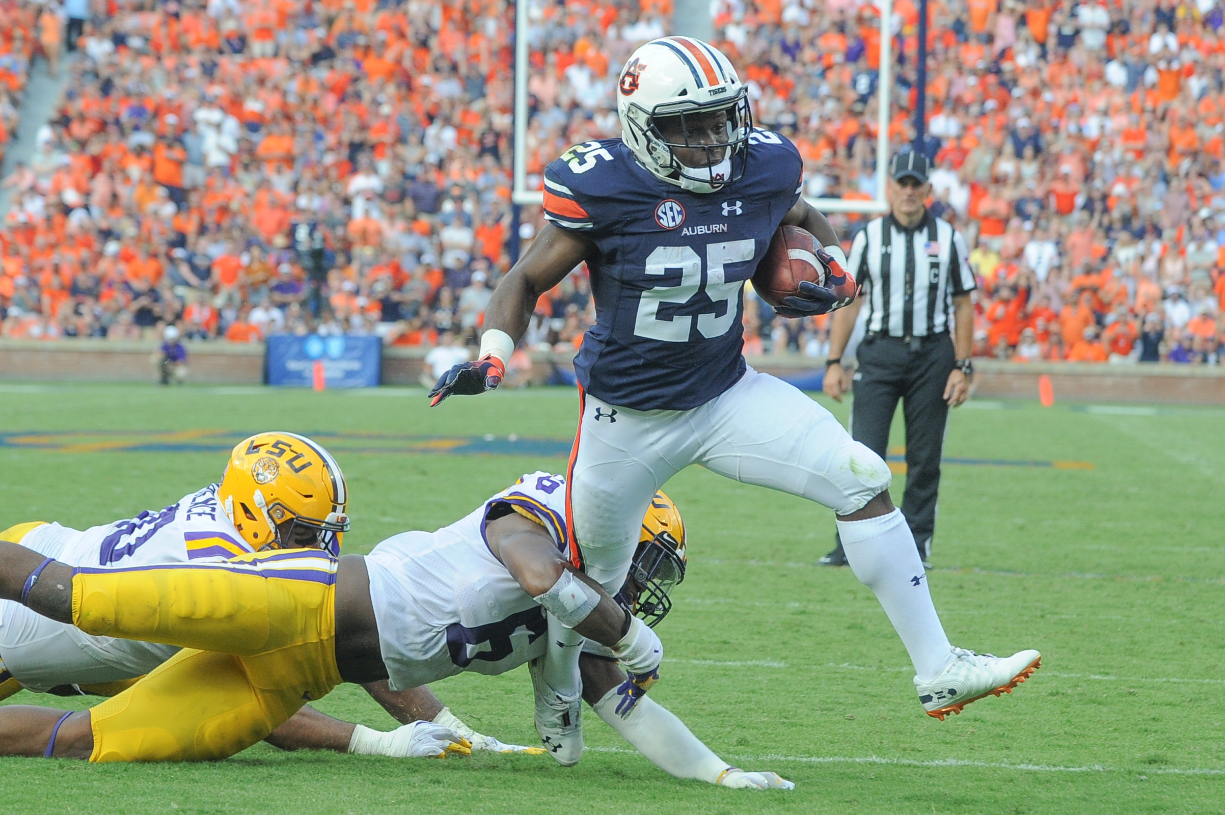 Auburn Tigers running back Shaun Shivers (25) breaks a tackle by LSU Tigers linebacker Jacob Phillips (6) during the first half of Saturday's game, at Jordan Hare Stadium in Auburn. (Contributed by Jeff Johnsey)