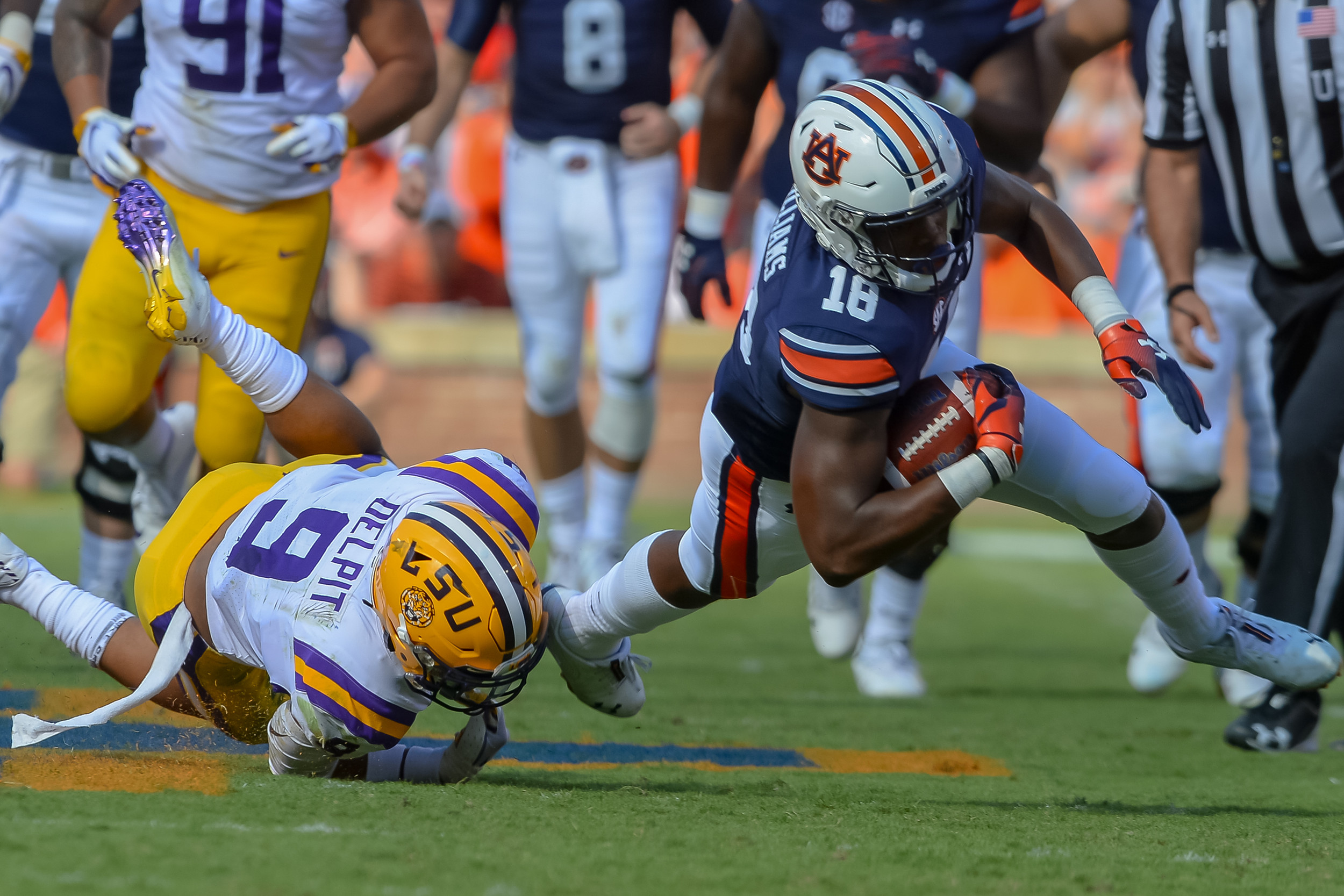 LSU Tigers safety Grant Delpit (9)trips up Auburn Tigers wide receiver Seth Williams (18) during the first half of Saturday's game, at Jordan Hare Stadium in Auburn. (Contributed by Jeff Johnsey)