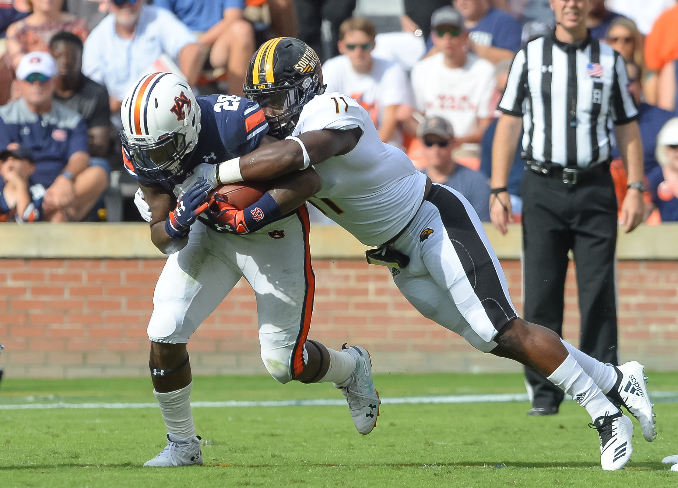 Auburn Tigers running back JaTarvious Whitlow (28) is tackled by Southern Miss Golden Eagles linebacker Sherrod Ruff (11) during the first half of Saturday's game, at Jordan Hare Stadium in Auburn AL. Daily Mountain Eagle -  Jeff Johnsey