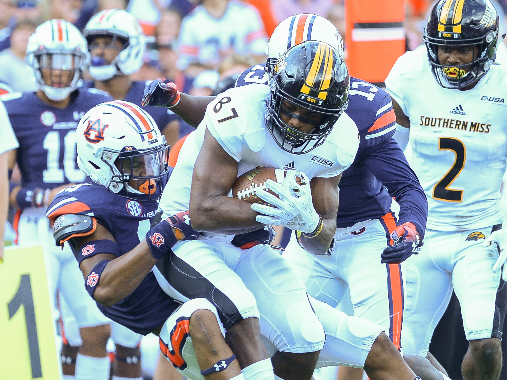 Southern Miss Golden Eagles wide receiver Tim Jones (87) is brought down by Auburn Tigers defensive backs Jordyn Peters (15) and Javaris Davis (13) during the first half of Saturday's game, at Jordan Hare Stadium in Auburn AL. Daily Mountain Eagle -  Jeff Johnsey