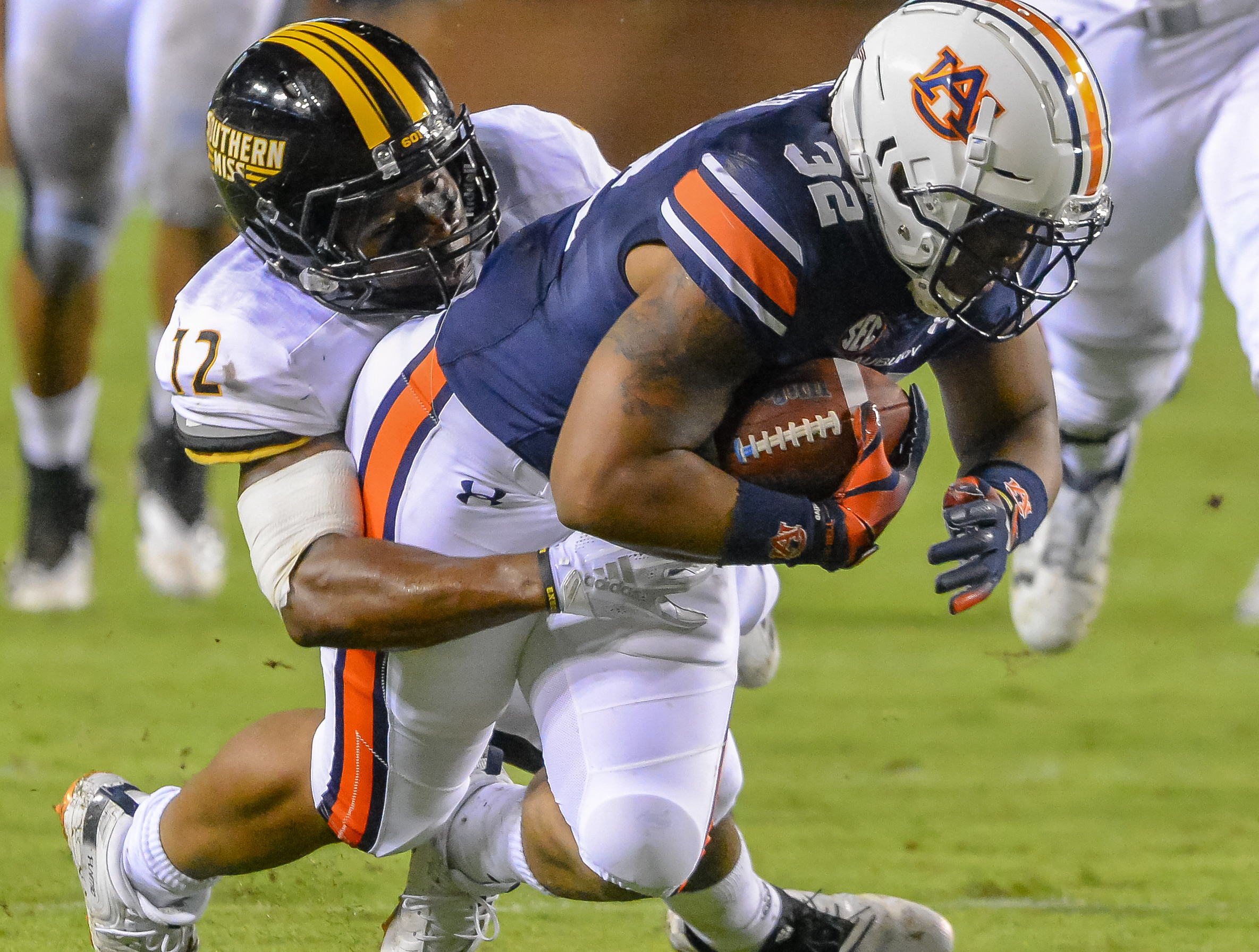 Southern Miss Golden Eagles defensive back D.Q. Thomas (12) brings down Auburn Tigers running back Malik Miller (32) during the second half of Saturday's game, at Jordan Hare Stadium in Auburn AL. Daily Mountain Eagle -  Jeff Johnsey
