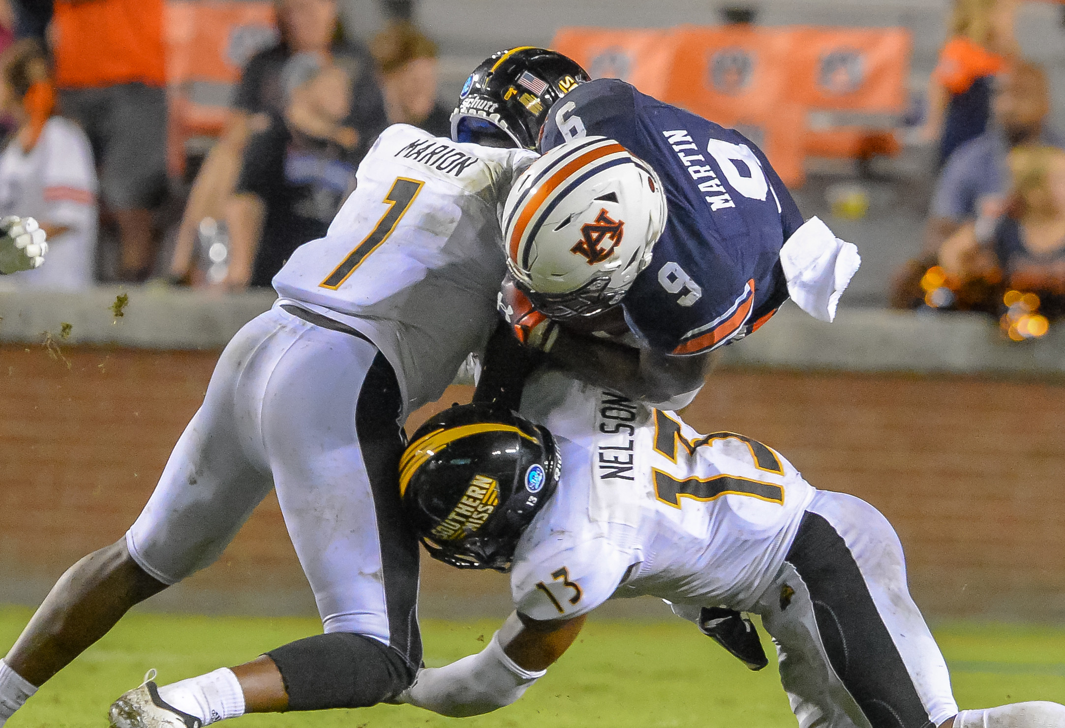 Southern Miss Golden Eagles defensive backs Xavier Marion (1) and Shannon Showers (15) combine to tackle Auburn Tigers running back Kam Martin (9) during the second half of Saturday's game, at Jordan Hare Stadium in Auburn AL. Daily Mountain Eagle -  Jeff Johnsey