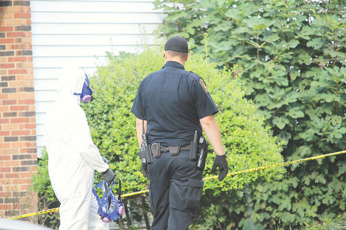 Members of Jasper Police Department's Crime Scene Unit wore hazmat suits while entering and exiting the residence where two bodies were discovered after officers performed a welfare check.