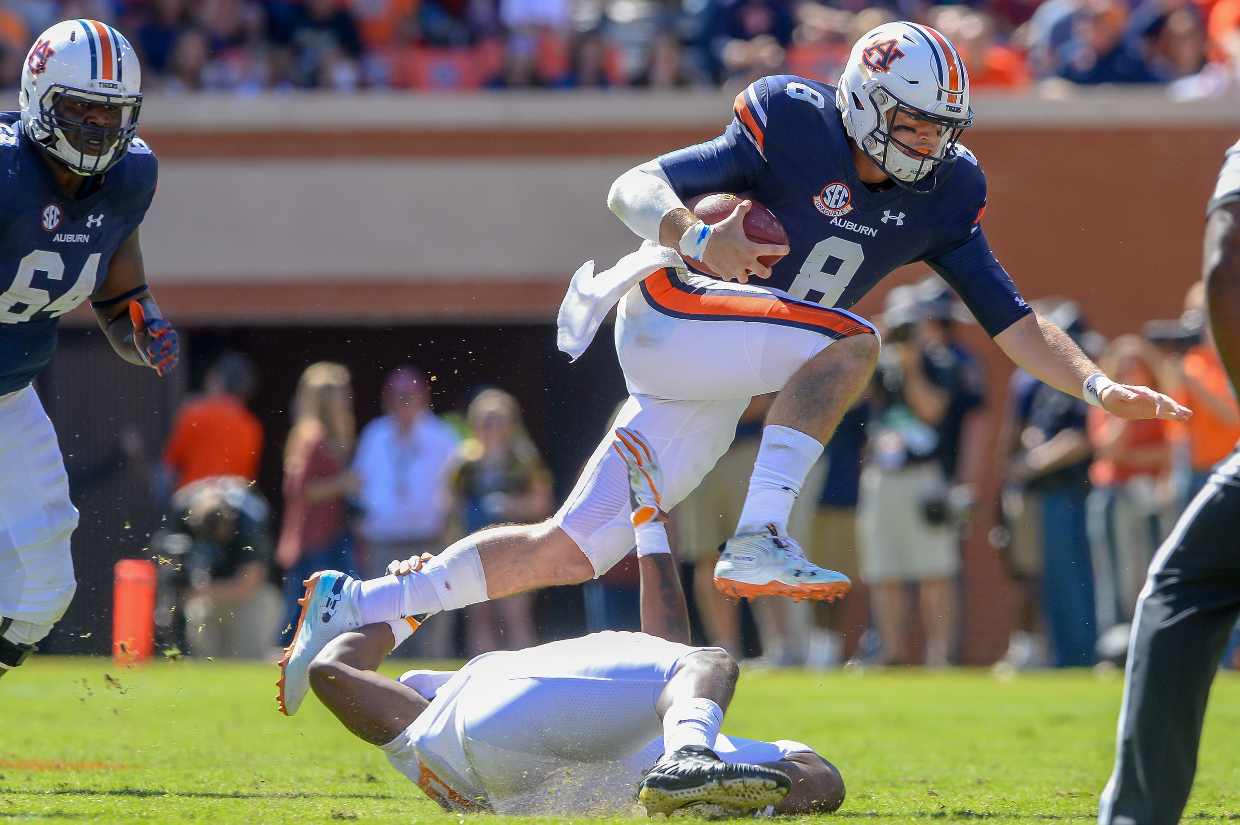 Auburn Tigers quarterback Jarrett Stidham (8) hurdles over Tennessee Volunteers linebacker Darrell Taylor (19) during the second half of Saturday's game, at Jordan-Hare Stadium in Auburn, AL. Daily Mountain Eagle -  Jeff Johnsey