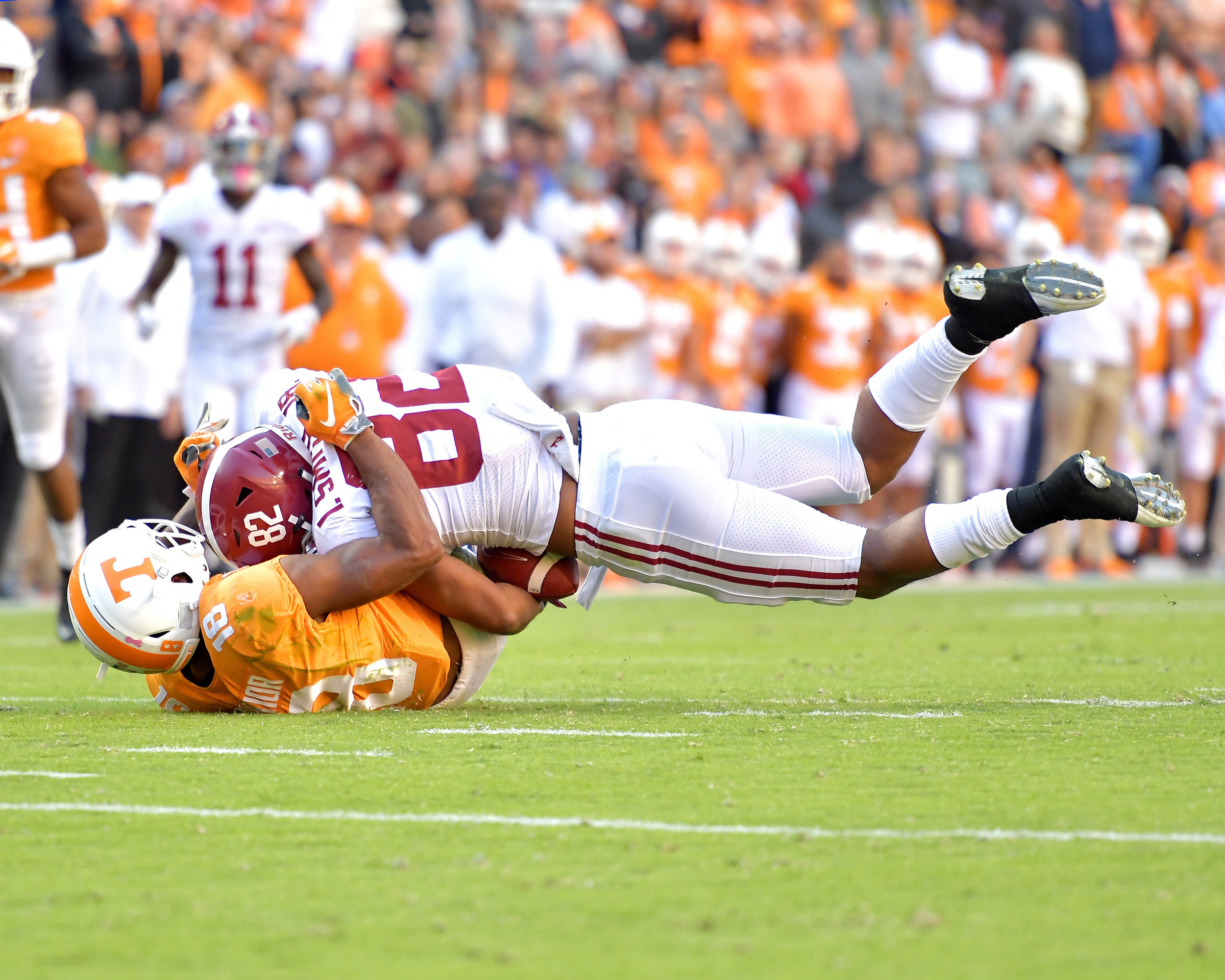 Alabama Crimson Tide tight end Irv Smith Jr. (82) is tackled by Tennessee Volunteers defensive back Nigel Warrior (18) in the second quarter of the NCAA football game on Saturday, Oct. 20, 2018, at Neyland Stadium in Knoxville. Tenn. Alabama wins 58-21. (Photo by Lee Walls)