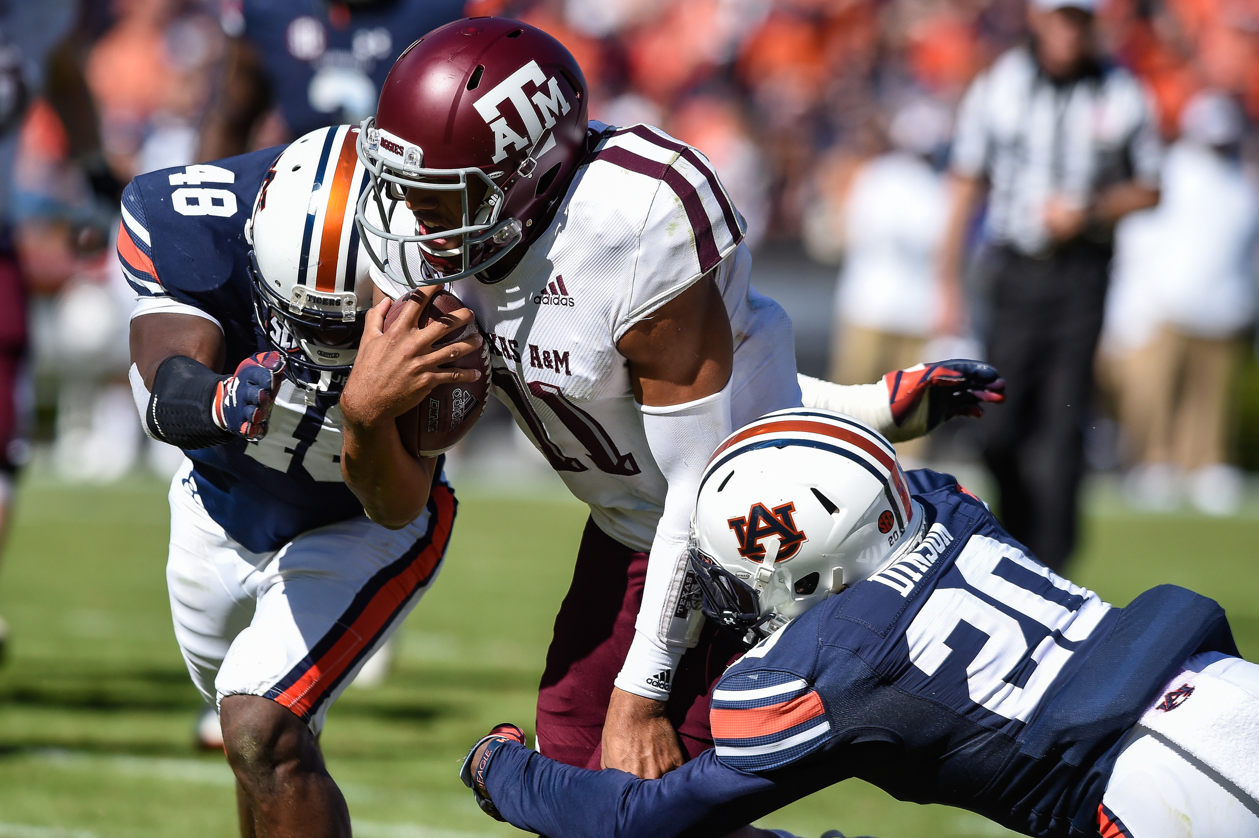 Auburn Tigers linebacker Montavious Atkinson (48) and  defensive back Jeremiah Dinson (20) tackle Texas A&M Aggies quarterback Kellen Mond (11) during the second half of an NCAA football game against the Texas A&M Aggies Saturday, November 3, 2018, at Jordan-Hare Stadium in Auburn, Ala. (Photo by Jeff Johnsey)
