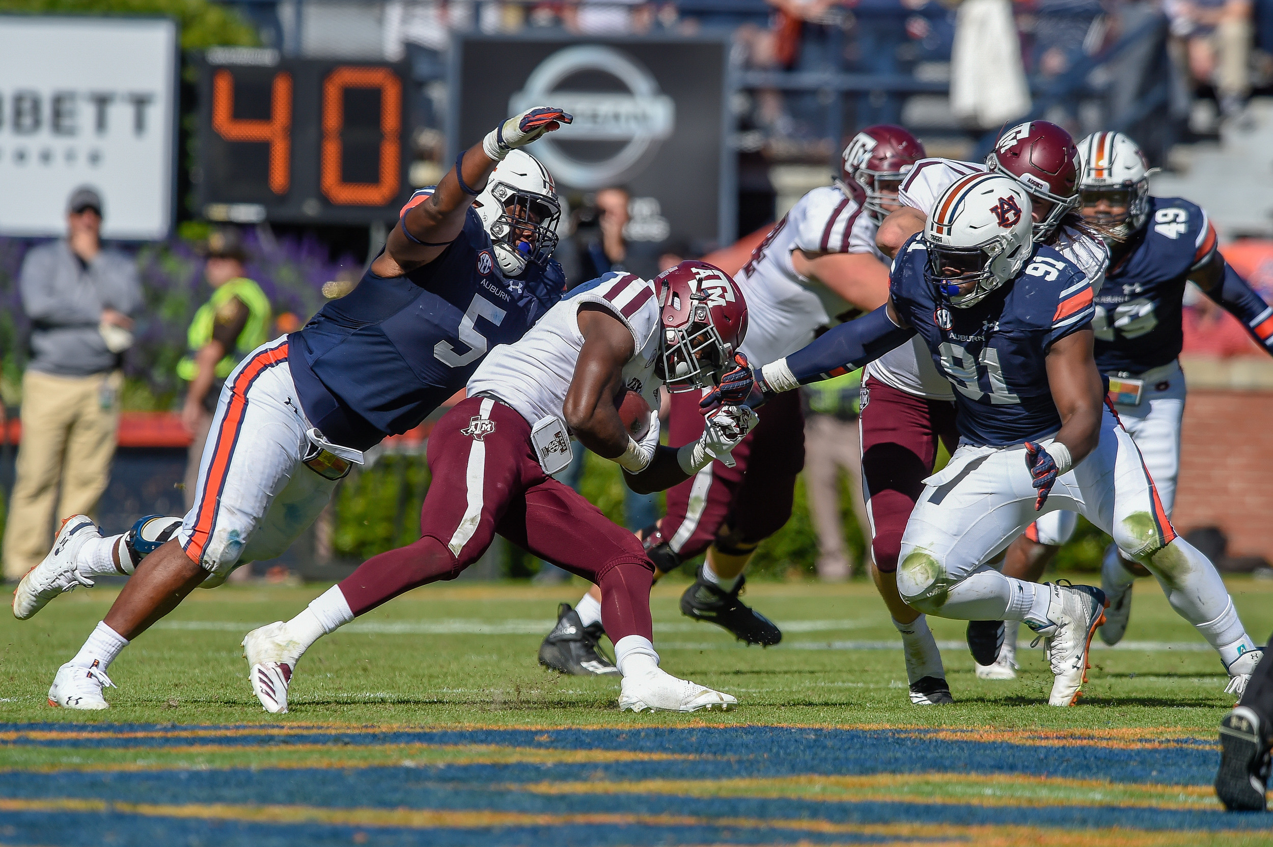 Auburn Tigers defensive linemen Derrick Brown (5) and  Nick Coe (91) bring down Texas A&M Aggies running back Jashaun Corbin (7) during the second half of an NCAA football game against the Texas A&M Aggies Saturday, November 3, 2018, at Jordan-Hare Stadium in Auburn, Ala. (Photo by Jeff Johnsey)