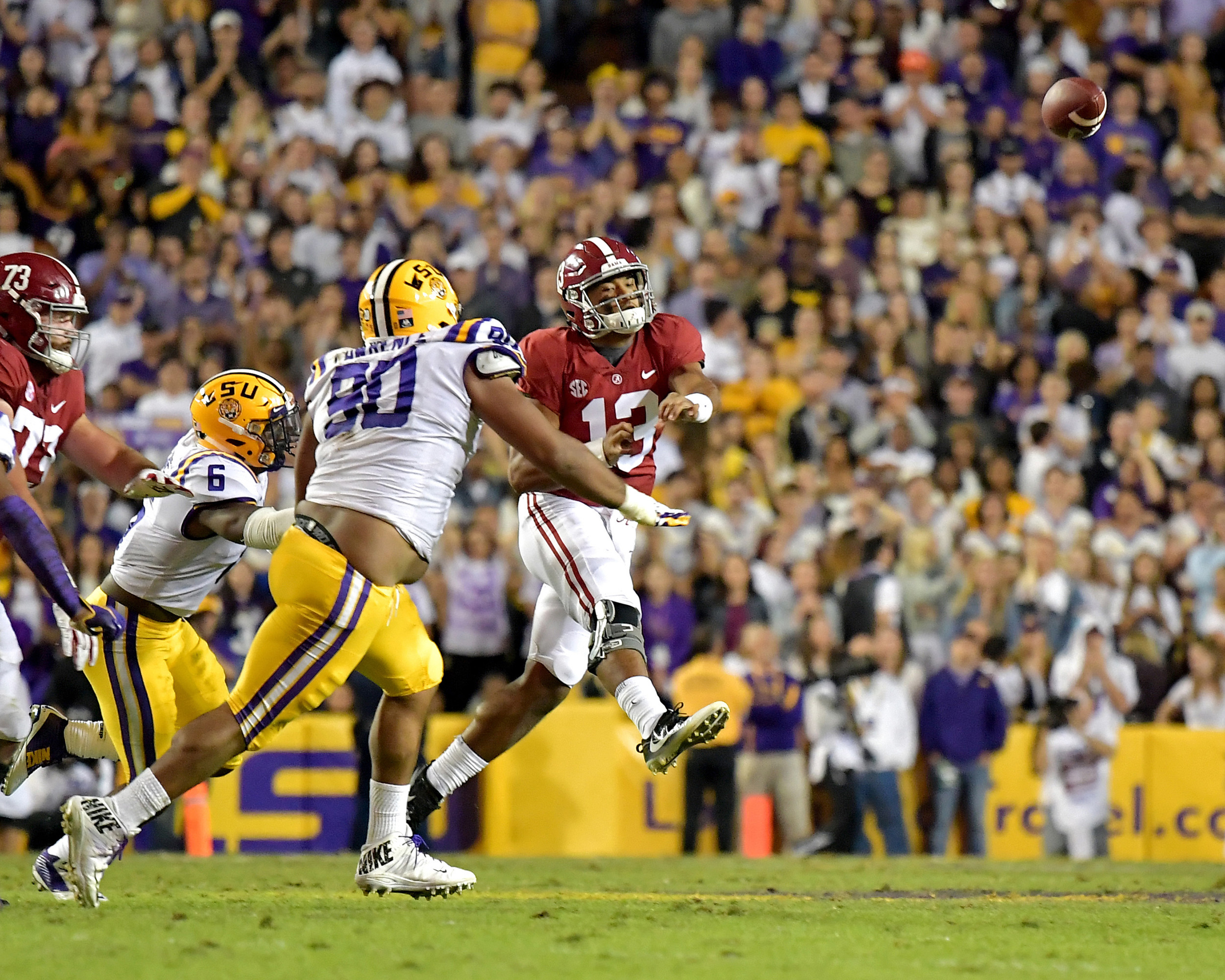 Alabama Crimson Tide quarterback Tua Tagovailoa (13) scrambles and passes under pressure in the first half of an NCAA football game against the LSU Tigers Saturday, November 3, 2018, at Tiger Stadium in Baton Rouge, La.