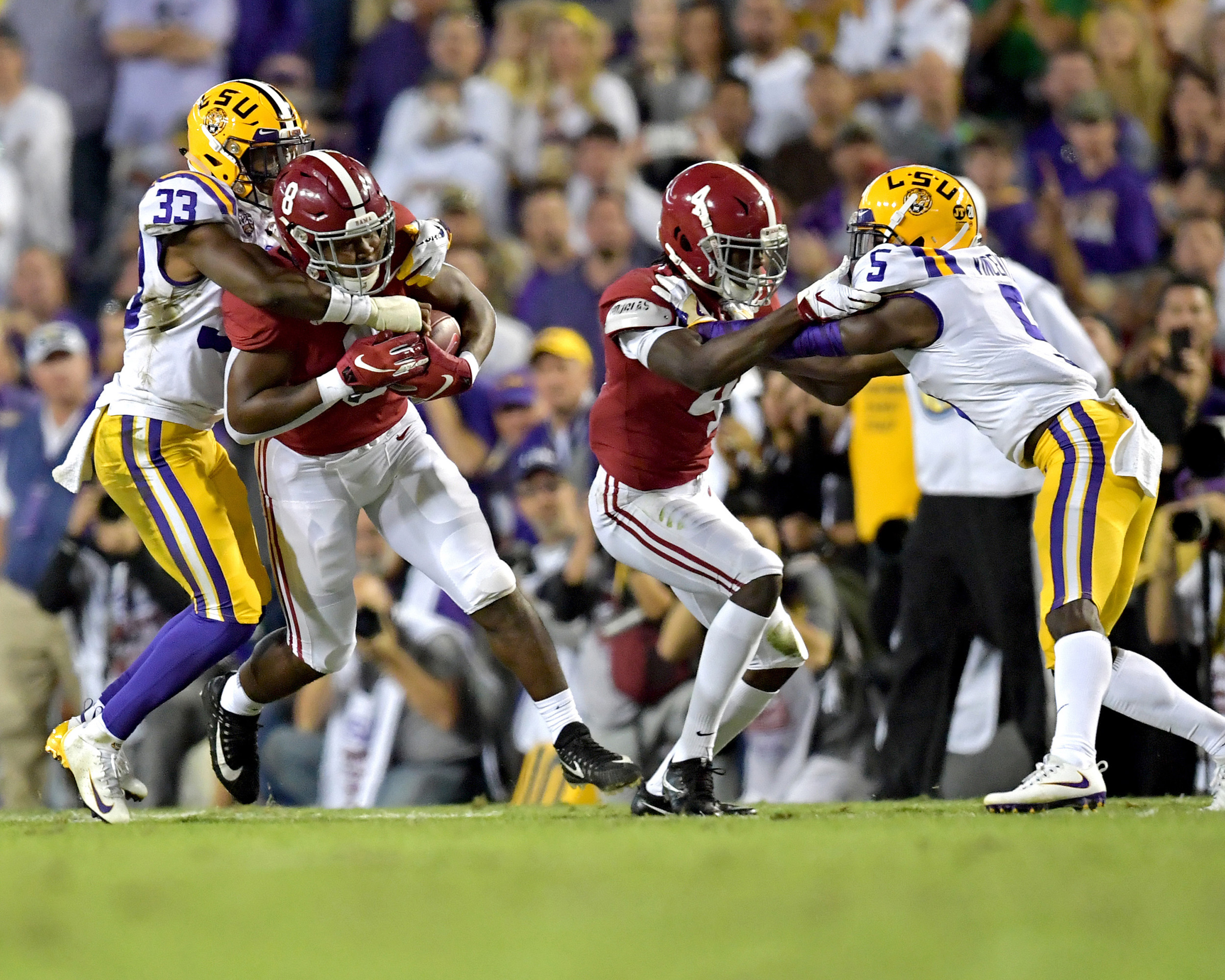 Alabama Crimson Tide running back Josh Jacobs (8) tries to avoid a tackle by LSU Tigers safety Todd Harris Jr. (33) in the first half of an NCAA football game Saturday, November 3, 2018, at Tiger Stadium in Baton Rouge, La.  Alabama wins 29-0. (Photo by Lee Walls)