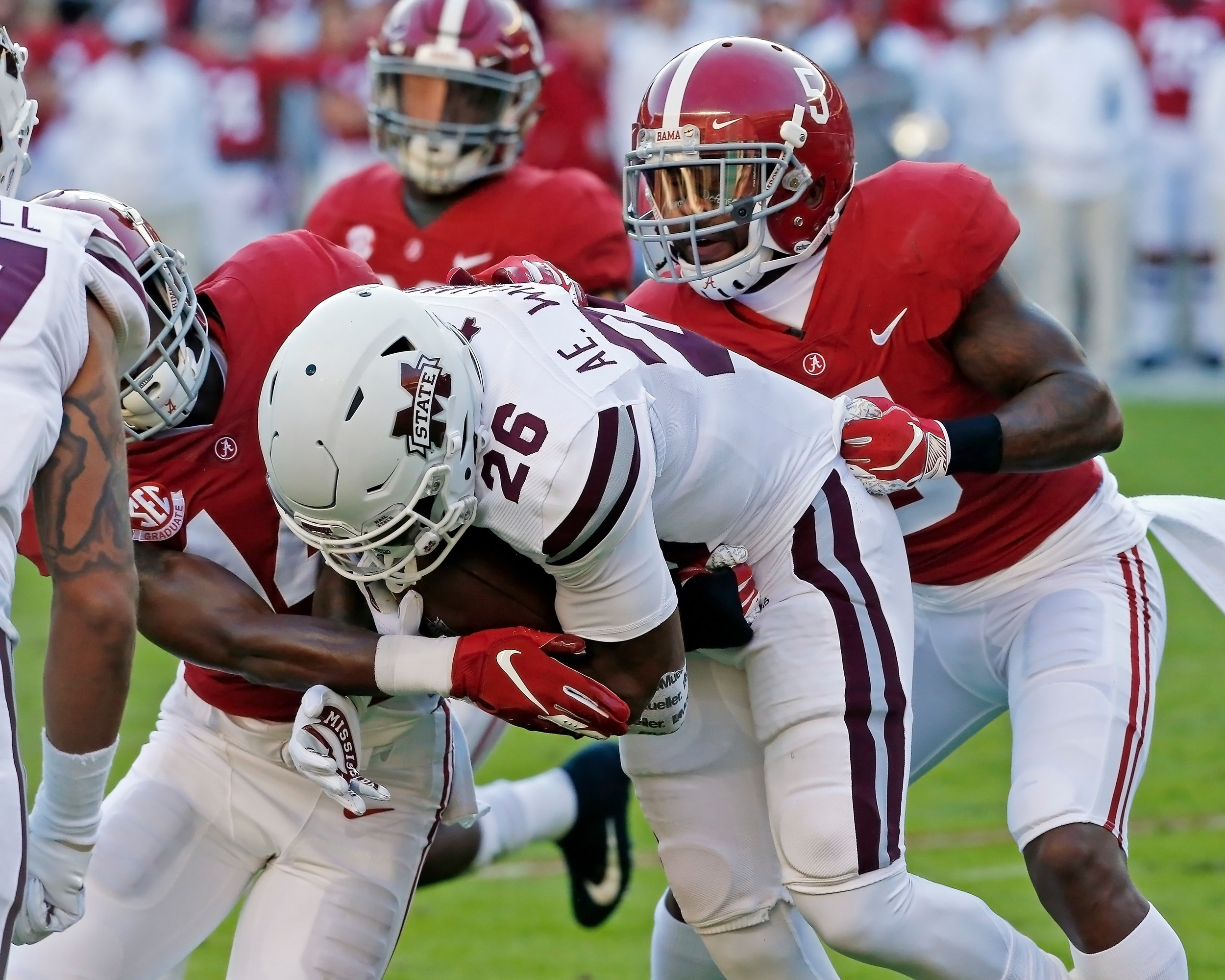 Mississippi State Bulldogs running back Aeris Williams (26) is wrapped up by Alabama Crimson Tide defensive backs Deionte Thompson (14) and  Shyheim Carter (5) during the game between Mississippi State and the University of Alabama at Bryant-Denny Stadium in Tuscaloosa, Al. Credit: Jason Clark / Daily Mountain Eagle