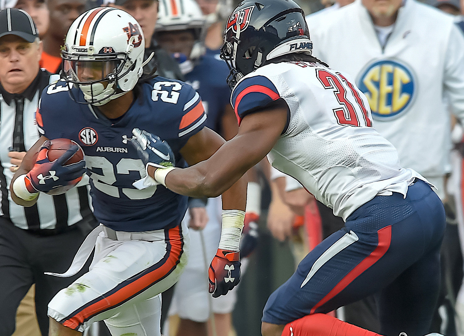 Auburn Tigers wide receiver Ryan Davis (23) is pushed pout of bounds by Liberty Flames safety Elijah Benton (31) during the first half of their game Saturday at Jordan-Hare Stadium in Auburn.