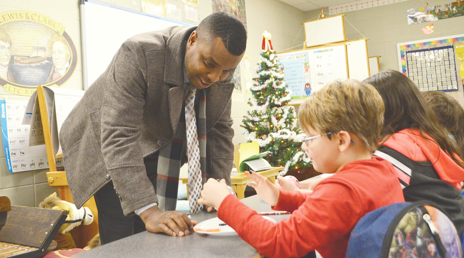 Oakman Mayor Cory Franks listens to a student talk about the ornament he painted at Oakman Middle School Tuesday.