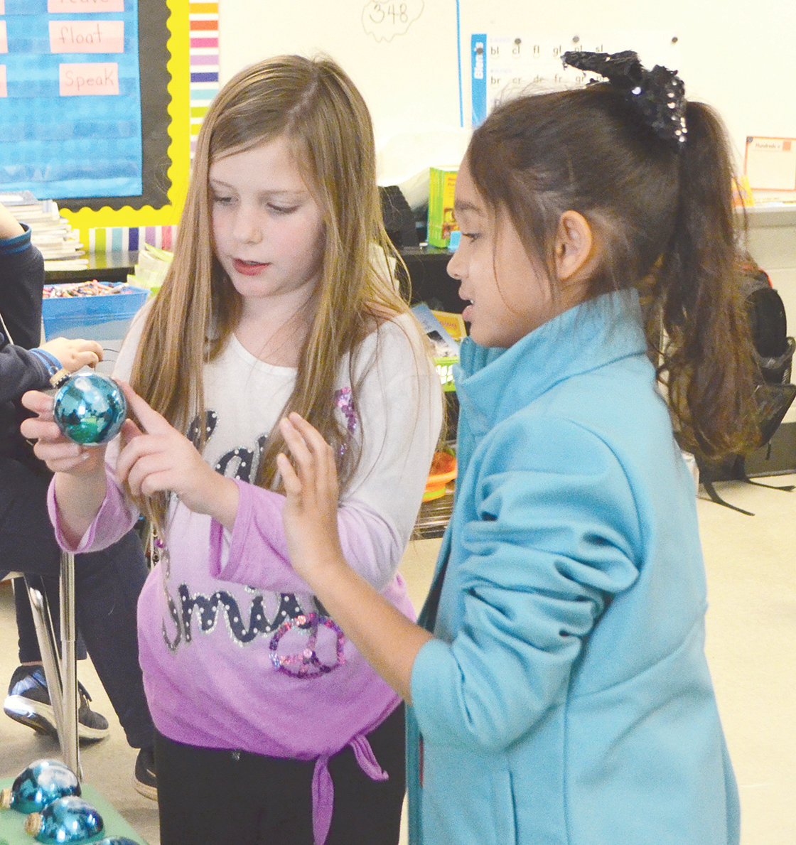 Two Oakman Middle School students make sure they are pleased with an ornament they painted Tuesday.