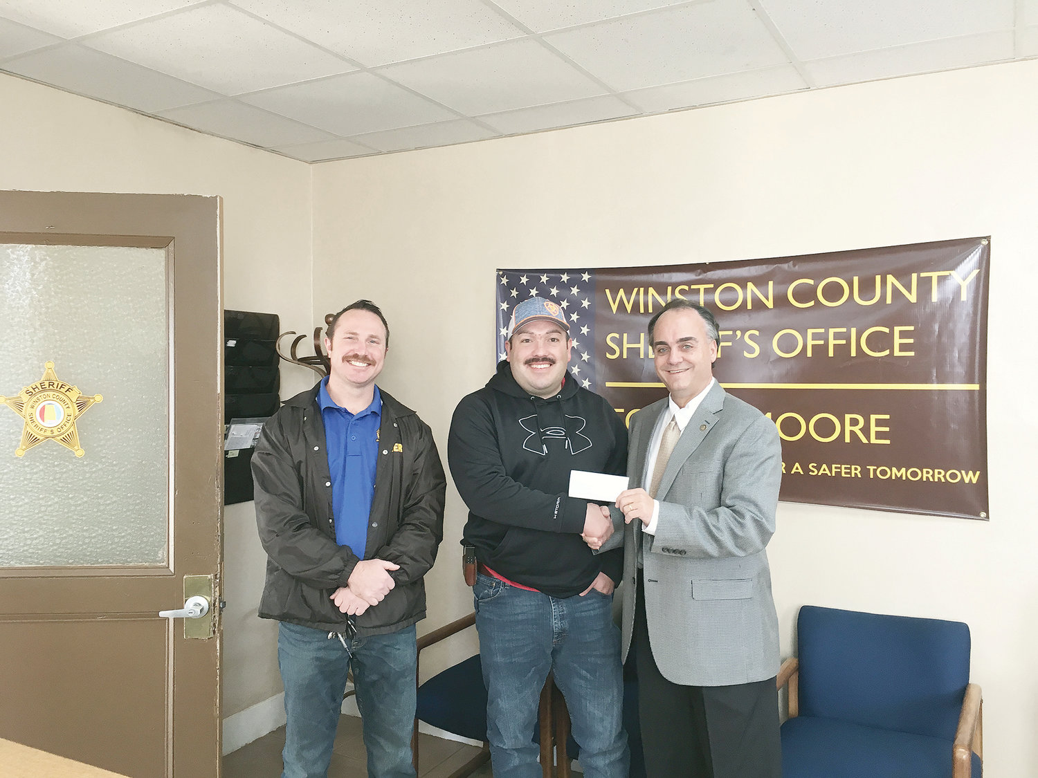During a Tuesday, Nov. 27, visit to Double Springs, state Rep. Tracy Estes, R-Winfield, right, presented $200 for the Winston County Fraternal Order of Police toy drive. Receiving the check are Caleb Snoddy and Brad Curtis of the Winston County Sheriff's Department.