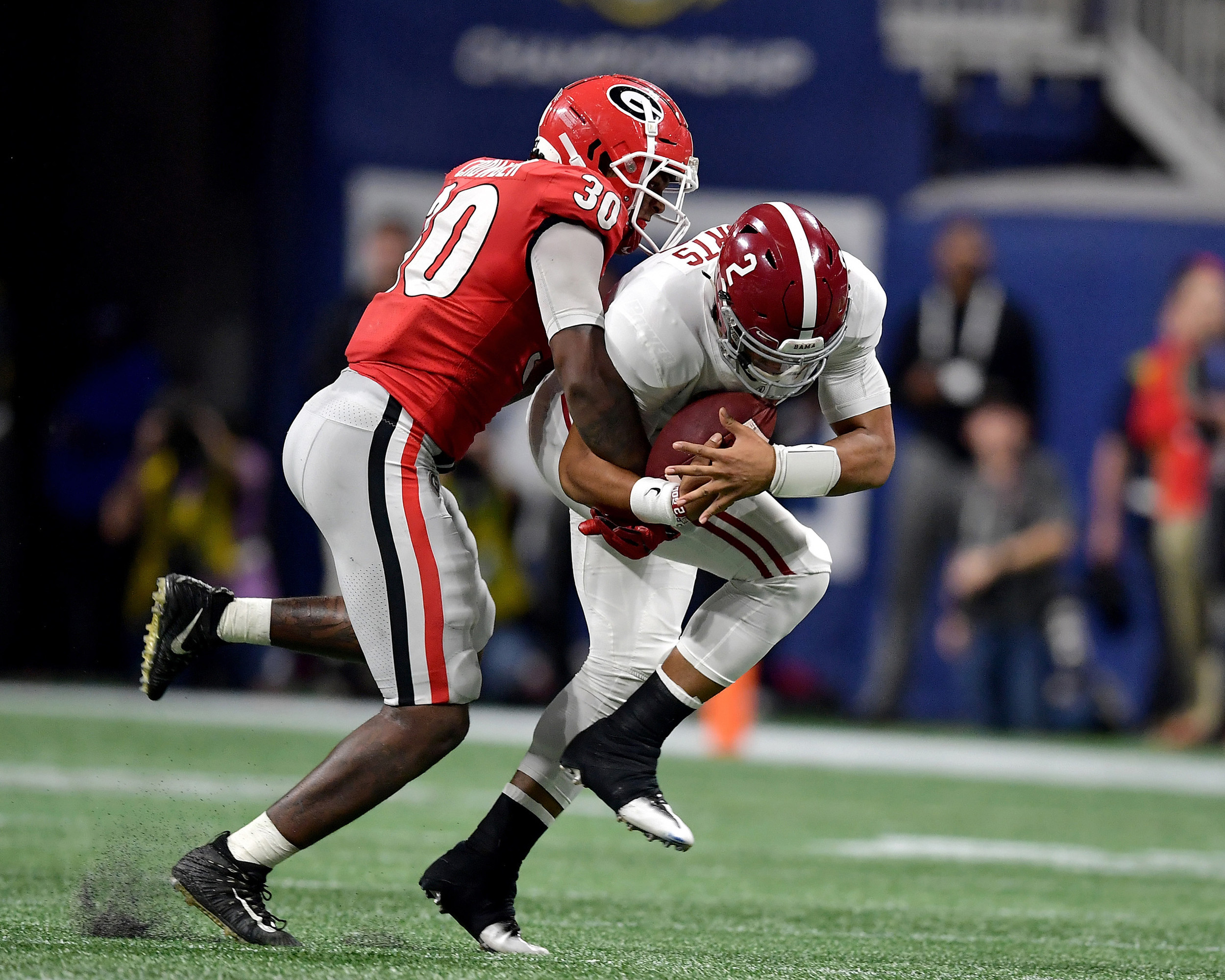 Alabama Crimson Tide quarterback Jalen Hurts (2) tries to avoid being tackled by Georgia Bulldogs linebacker Tae Crowder (30) in the fourth quarter of the 2018 SEC Championship football game at Mercedes-Benz Stadium in Atlanta, Ga., on Dec. 1, 2018. Alabama wins 35-28. (Photo by Lee Walls)