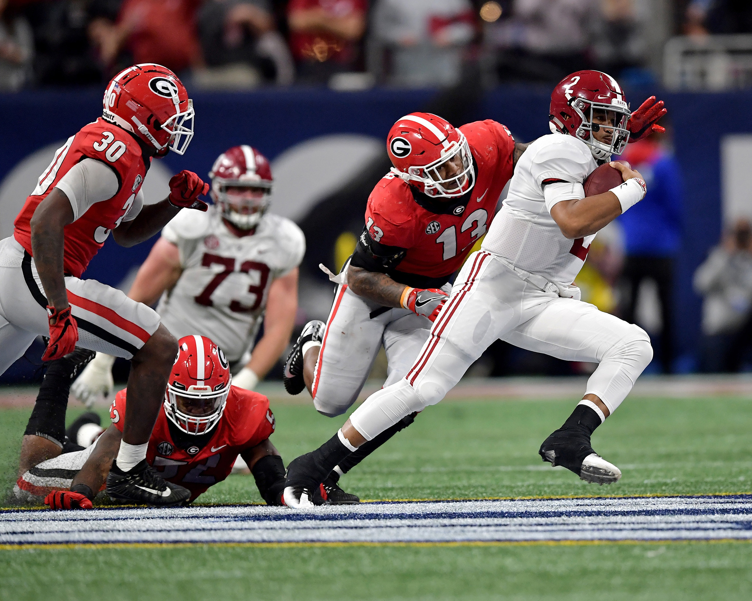 Alabama Crimson Tide quarterback Jalen Hurts (2) avoids a tackle by Georgia Bulldogs defensive end Jonathan Ledbetter (13) in the fourth quarter pf the 2018 SEC Championship football game at Mercedes-Benz Stadium in Atlanta, Ga., on Dec. 1, 2018. Alabama wins 35-28. (Photo by Lee Walls)
