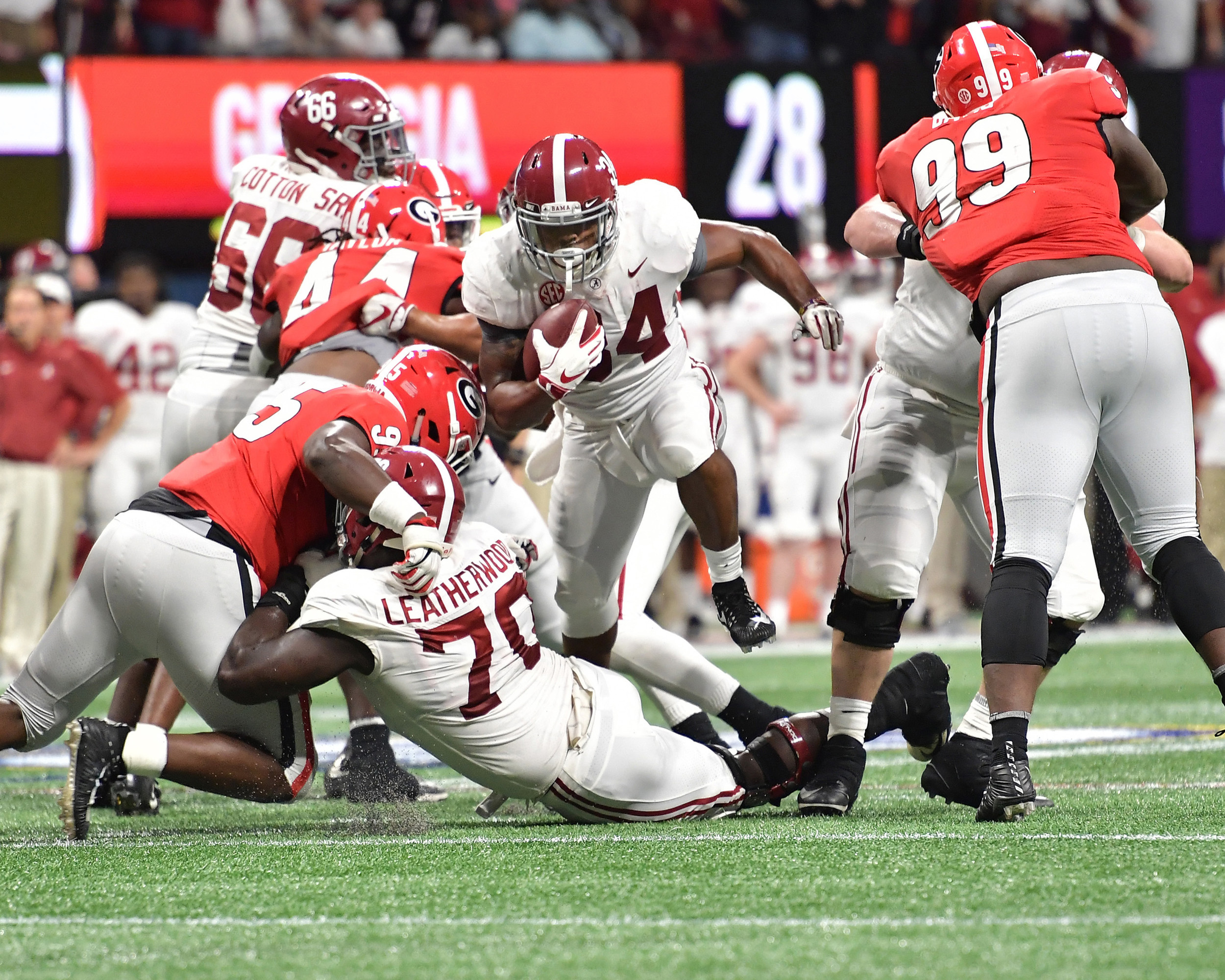 Alabama Crimson Tide running back Damien Harris (34) finds room to run late in the fourth quarter of the 2018 SEC Championship football game against the Georgia Bulldogs at Mercedes-Benz Stadium in Atlanta, Ga., on Dec. 1, 2018. Alabama wins 35-28. (Photo by Lee Walls)