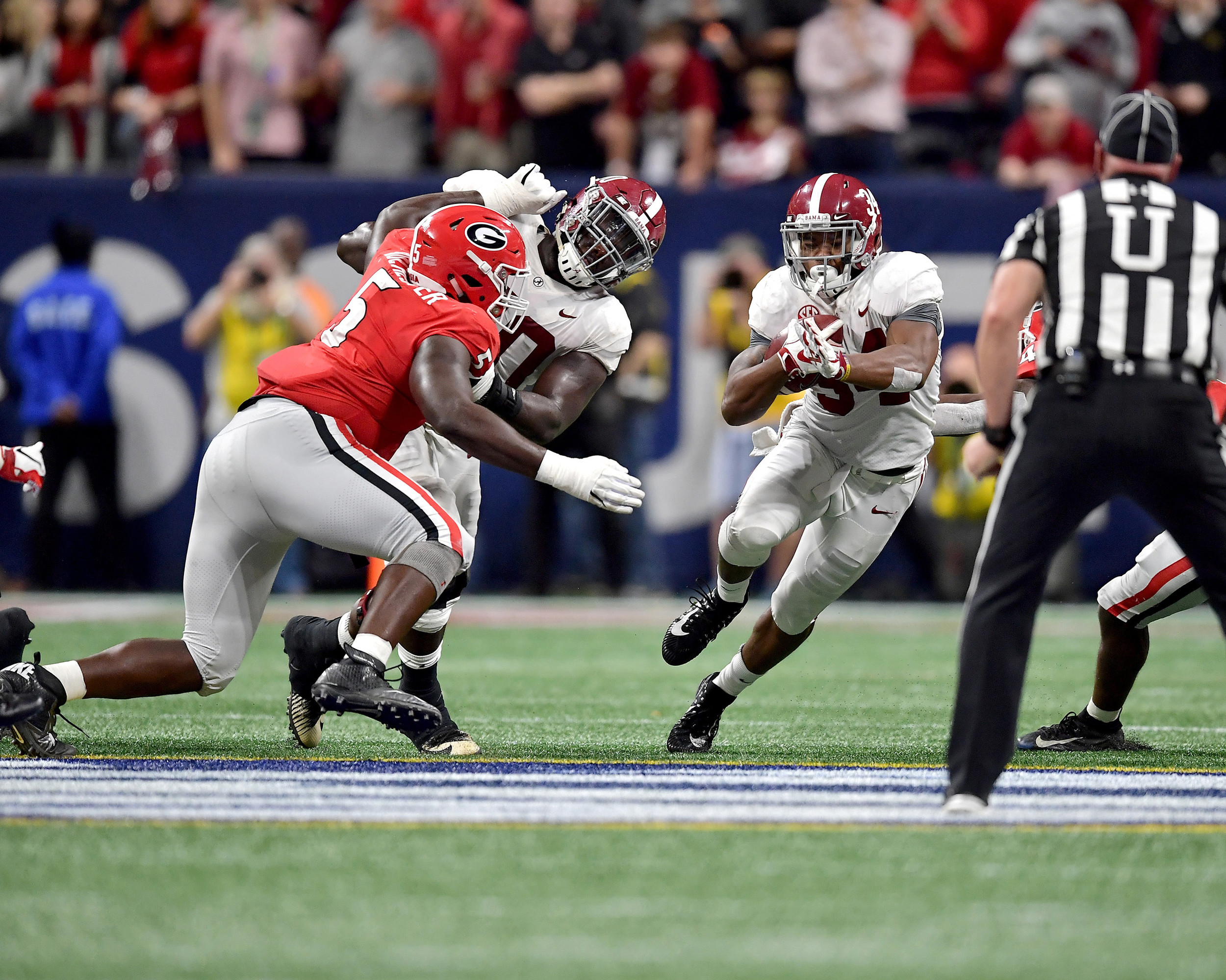Alabama Crimson Tide running back Damien Harris (34) runs up the middle during the fourth quarter of the 2018 SEC Championship football game against the Georgia Bulldogs at Mercedes-Benz Stadium in Atlanta, Ga., on Dec. 1, 2018. Alabama wins 35-28. (Photo by Lee Walls)