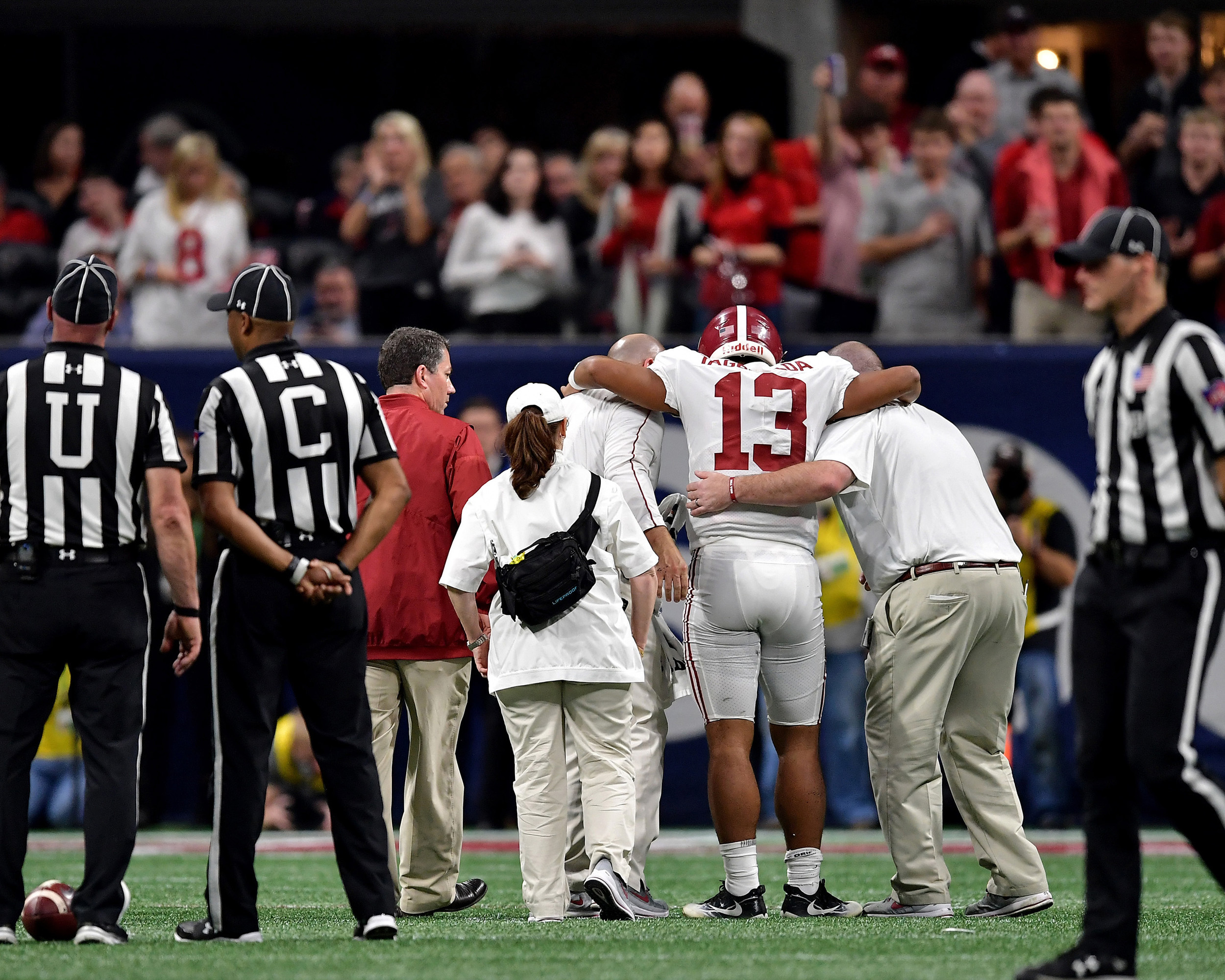 Alabama Crimson Tide quarterback Tua Tagovailoa (13) leaves the game with an ankle injury during the fourth quarter of the 2018 SEC Championship football game against the Georgia Bulldogs at Mercedes-Benz Stadium in Atlanta, Ga., on Dec. 1, 2018. Alabama wins 35-28. (Photo by Lee Walls)