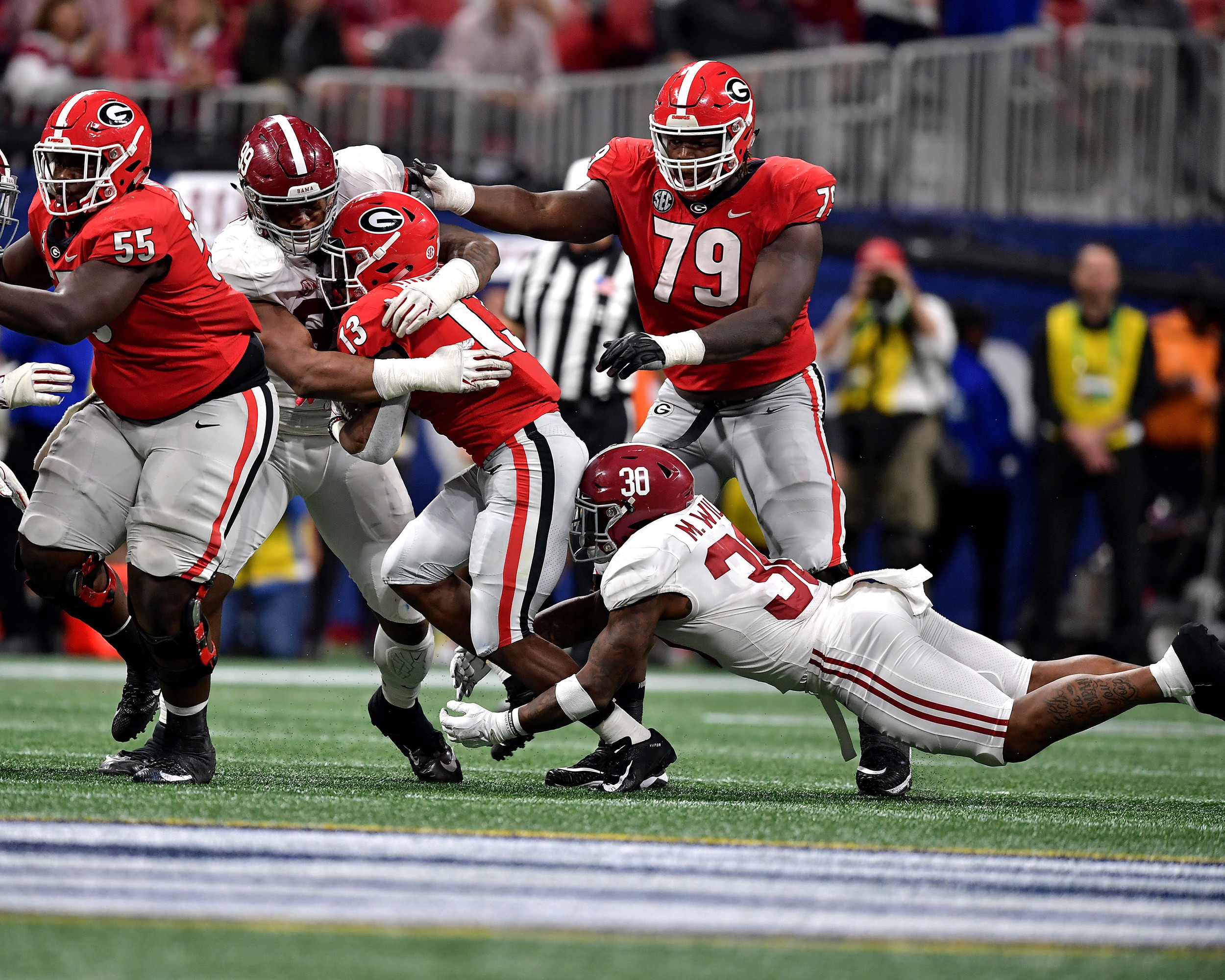 Georgia Bulldogs running back Elijah Holyfield (13) is covered up in the second half of the 2018 SEC Championship football game against the Alabama Crimson Tide at Mercedes-Benz Stadium in Atlanta, Ga., on Dec. 1, 2018. Alabama wins 35-28. (Photo by Lee Walls)