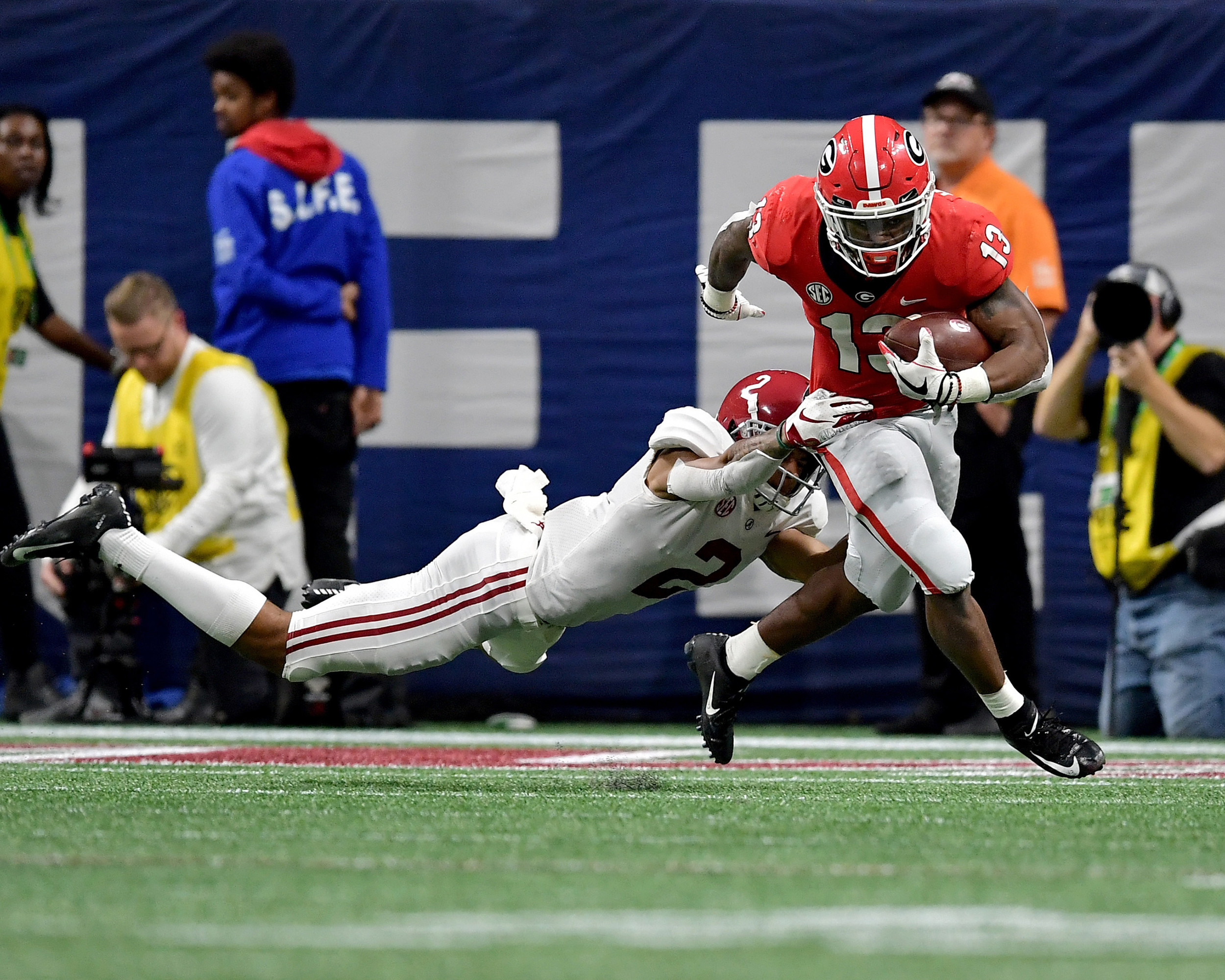Alabama Crimson Tide defensive back Patrick Surtain II (2) misses the tackle of Georgia Bulldogs running back Elijah Holyfield (13) during the second half of the 2018 SEC Championship football game at Mercedes-Benz Stadium in Atlanta, Ga., on Dec. 1, 2018. Alabama wins 35-28. (Photo by Lee Walls)