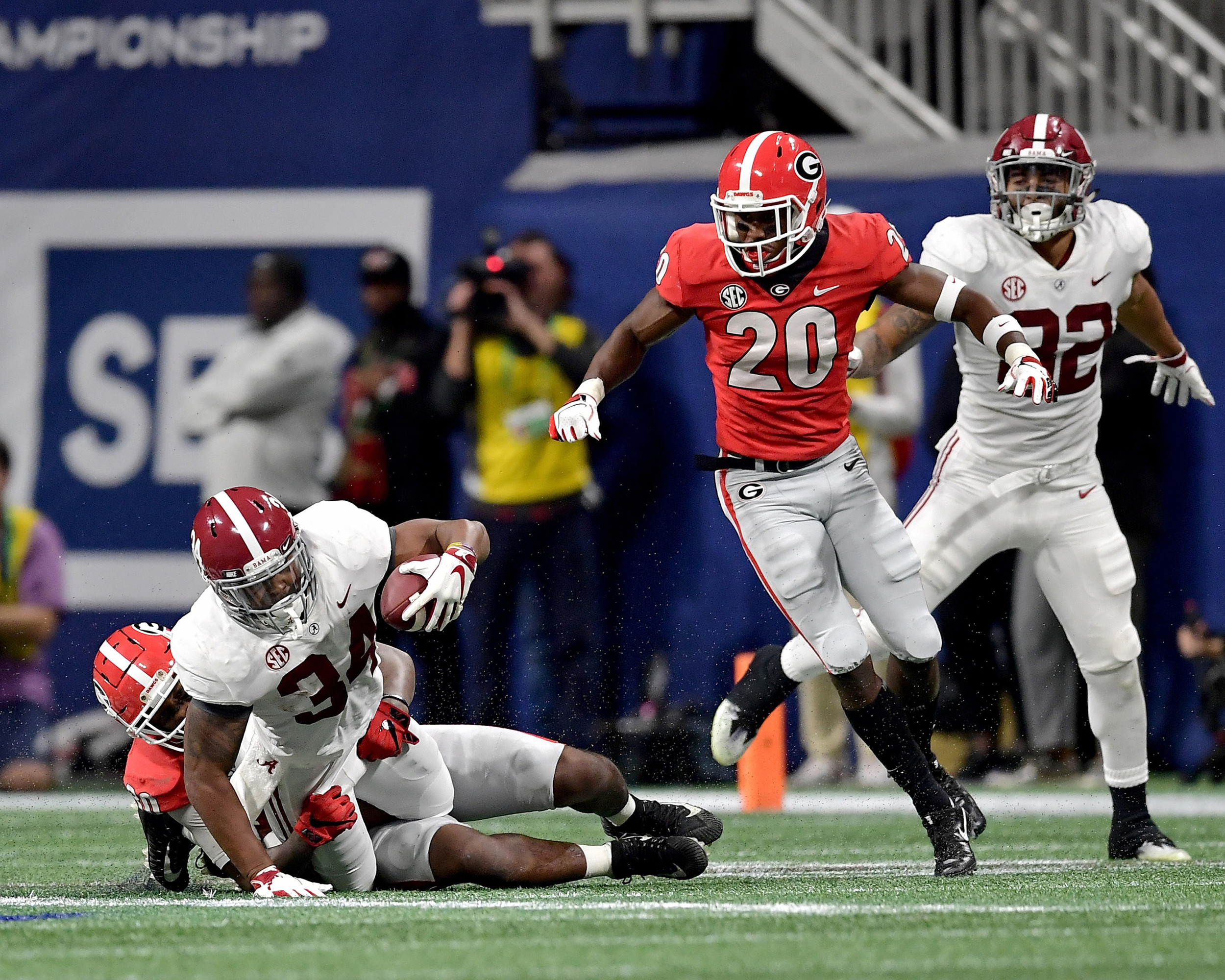 Alabama Crimson Tide running back Damien Harris (34) is tackled during the first half of the 2018 SEC Championship football game against the Georgia Bulldogs at Mercedes-Benz Stadium in Atlanta, Ga., on Dec. 1, 2018. Alabama wins 35-28. (Photo by Lee Walls)
