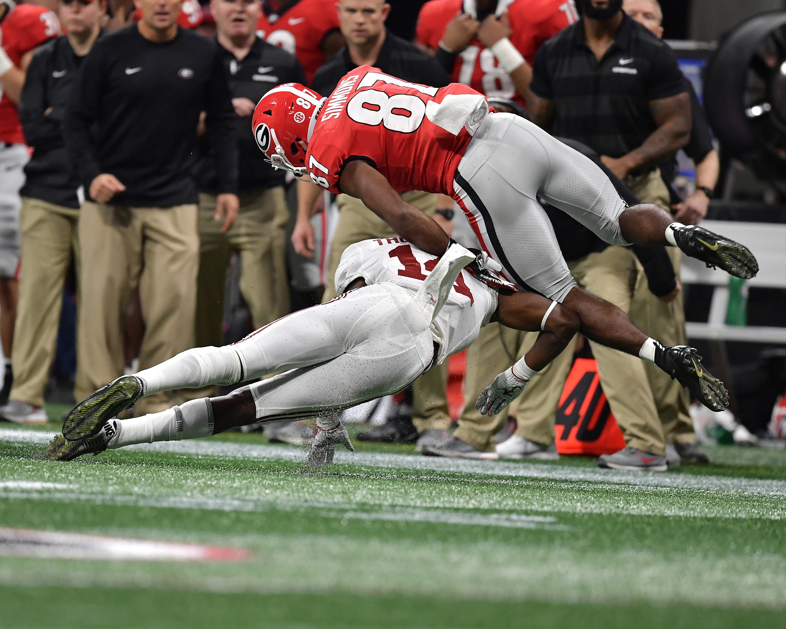 Alabama Crimson Tide defensive back Deionte Thompson (14) tackles Georgia Bulldogs wide receiver Tyler Simmons (87) in the first half of the 2018 SEC Championship football game at Mercedes-Benz Stadium in Atlanta, Ga., on Dec. 1, 2018. Alabama wins 35-28. (Photo by Lee Walls)