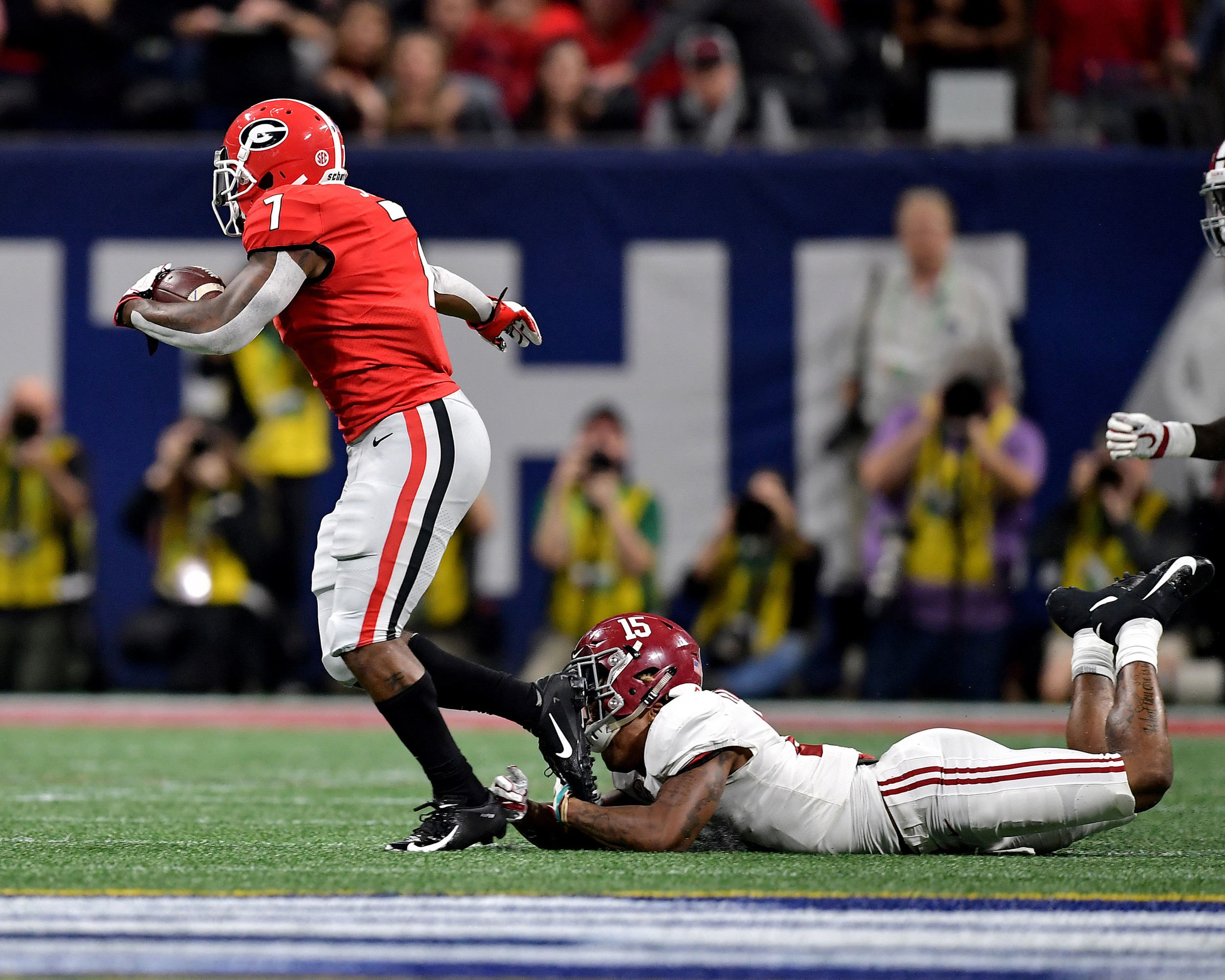 Alabama Crimson Tide defensive back Xavier McKinney (15) tries to tackle Georgia Bulldogs running back D'Andre Swift (7) during the first half of the 2018 SEC Championship football game at Mercedes-Benz Stadium in Atlanta, Ga., on Dec. 1, 2018. Alabama wins 35-28. (Photo by Lee Walls)