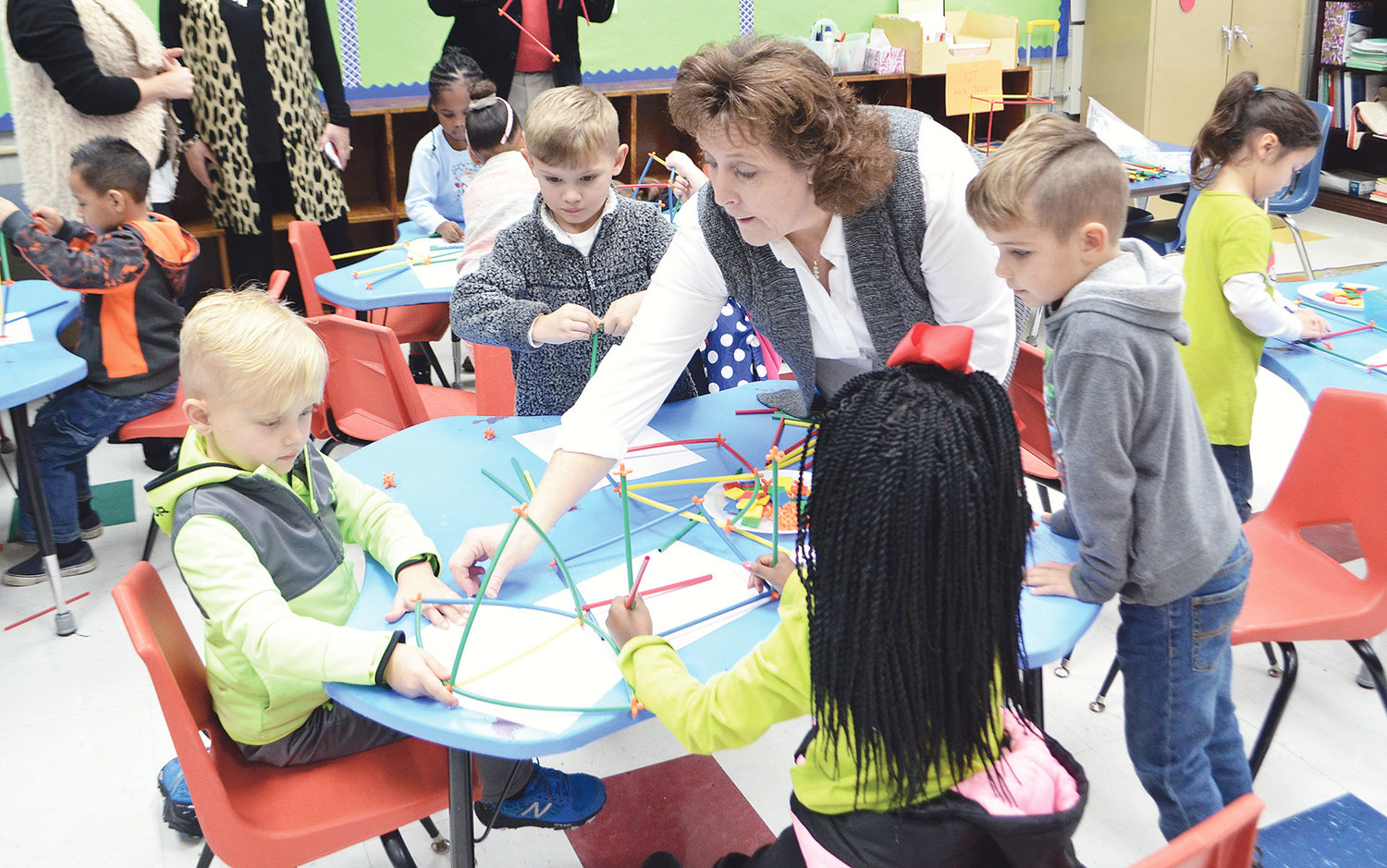Volunteer teacher Vicki Howard helps students with a STEM project at T.R. Simmons Elementary.