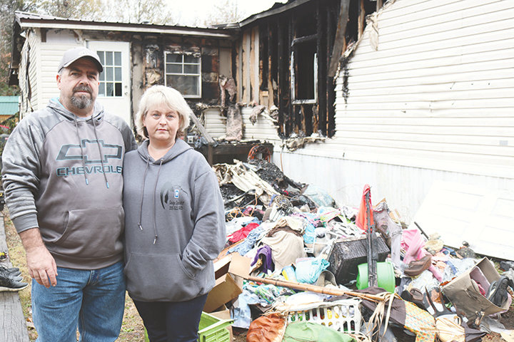 James and Rebecca Cooper stand in front of their home that was destroyed by fire the week before Thanksgiving.