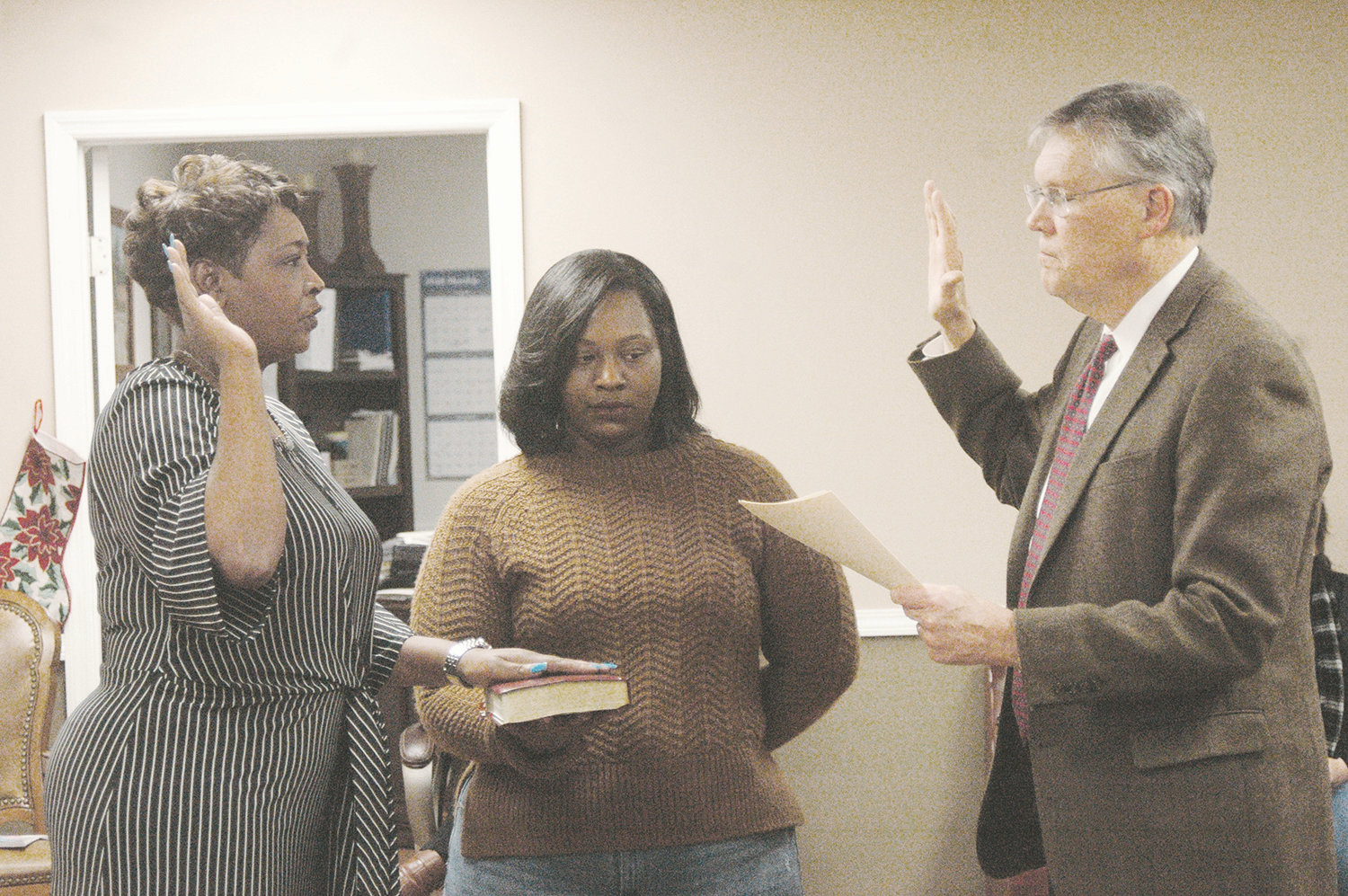 Walker County Circuit Judge Hoyt Elliott, right, swears-in new Parrish Town Council member La'Tisha Oliver, left, on Tuesday night. Oliver will represent District 4.  Oliver's daughter is holding the Bible.