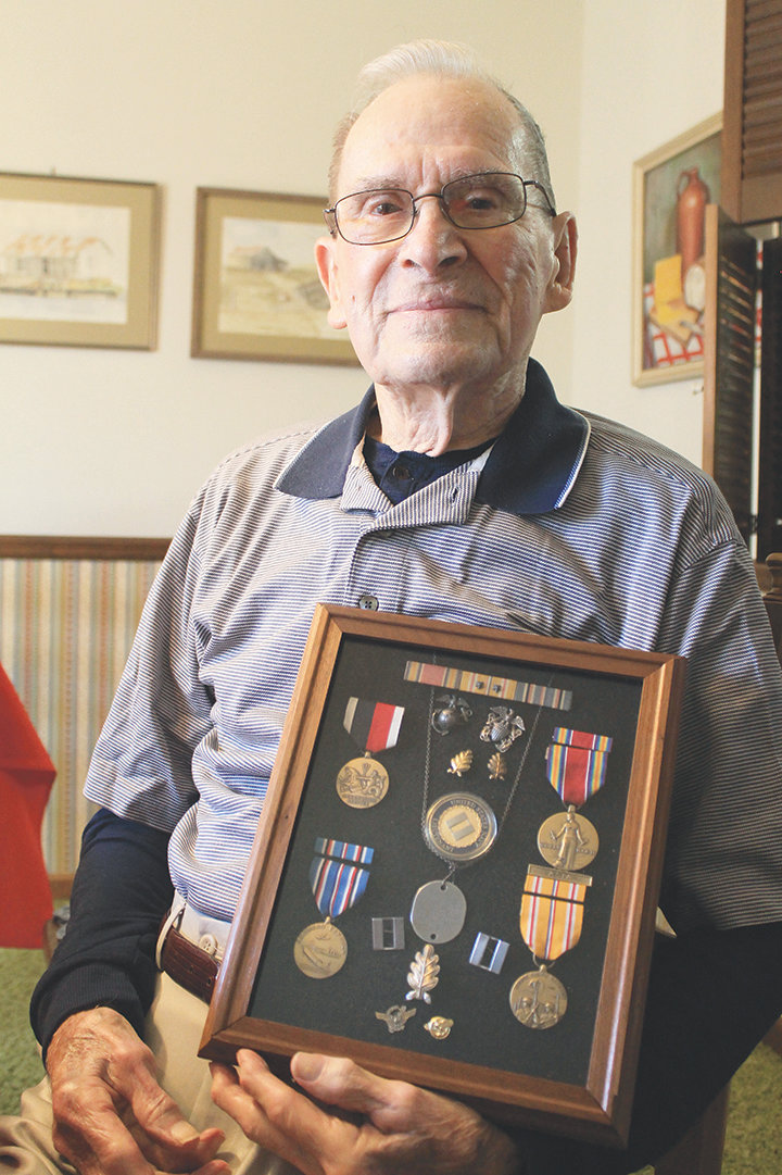 Dr. Doyce Briscoe holds his World War II medals on Tuesday, his 99th birthday. Briscoe served with the 2nd Marine Division in the Pacific theater.