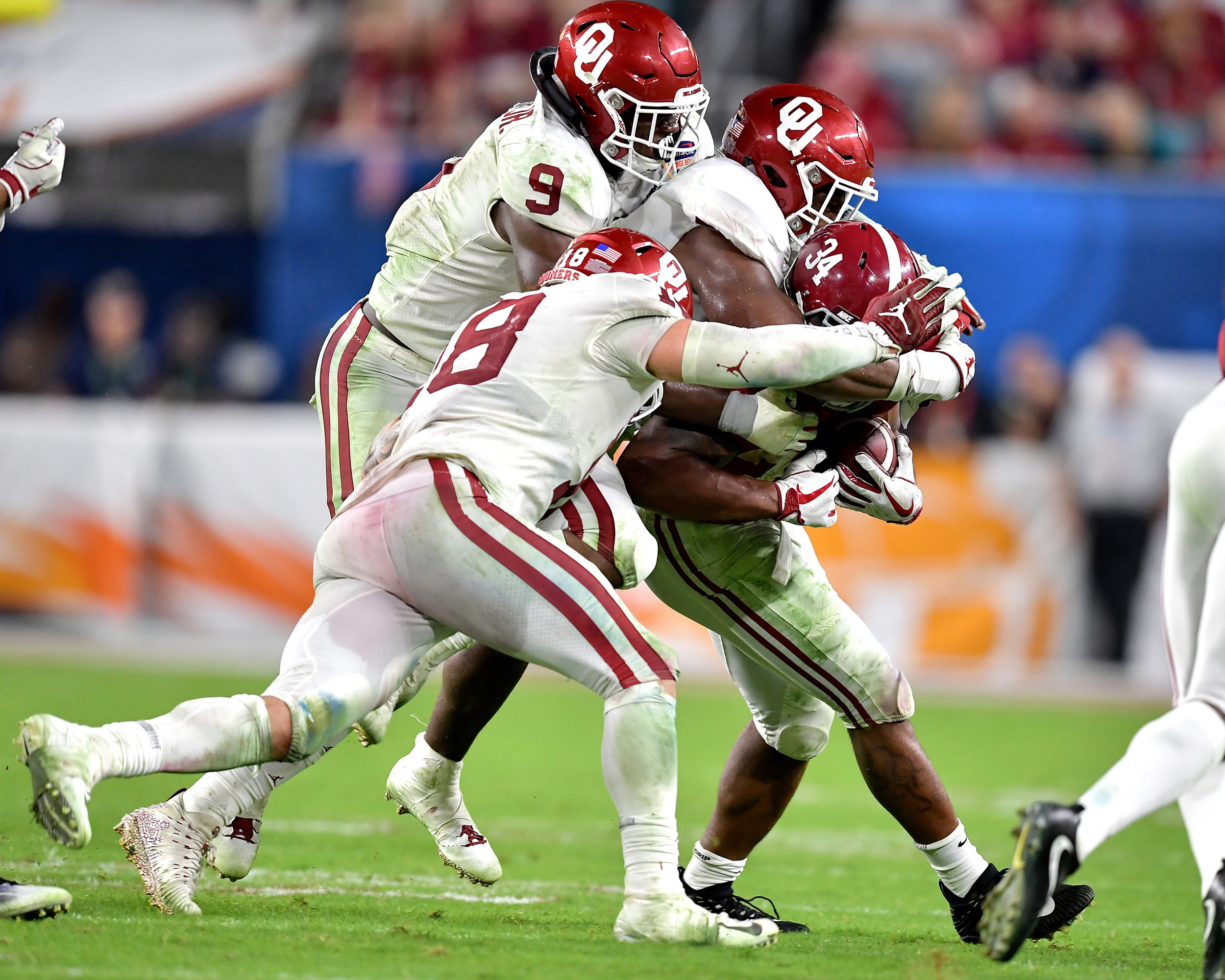 It takes three Oklahoma Sooners to tackle Alabama Crimson Tide running back Damien Harris (34) in the second half of the Capital One Orange Bowl at Hard Rock Stadium in Miami Gardens, Fla., Saturday, Dec. 29, 2018. Alabama wins 45-34. (Photo by Lee Walls)