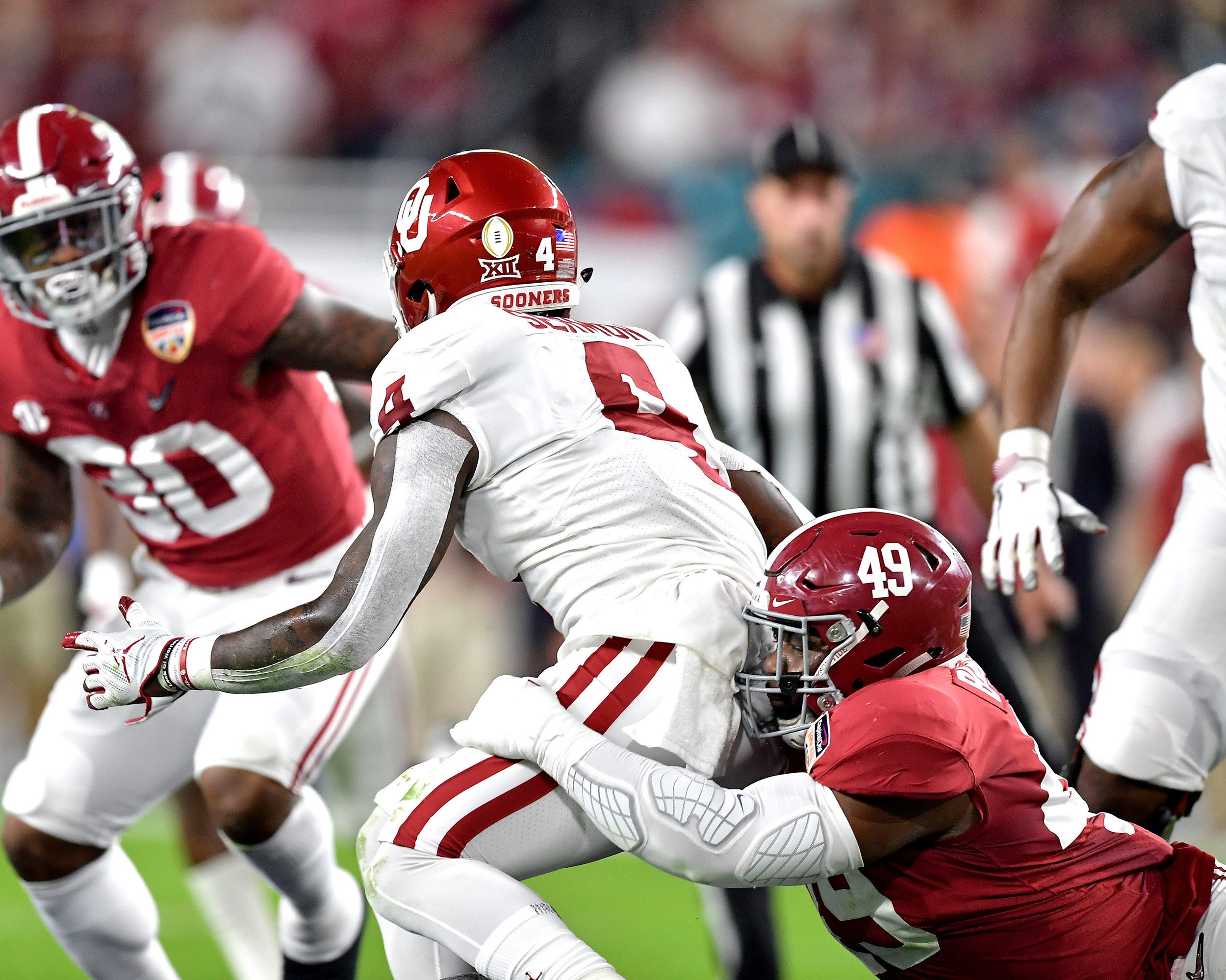Alabama Crimson Tide defensive lineman Isaiah Buggs (49) tackles Oklahoma Sooners running back Trey Sermon (4) behind the line of scrimmage during the first half of the Capital One Orange Bowl at Hard Rock Stadium in Miami Gardens, Fla., Saturday, Dec. 29, 2018. Alabama wins 45-34. (Photo by Lee Walls)