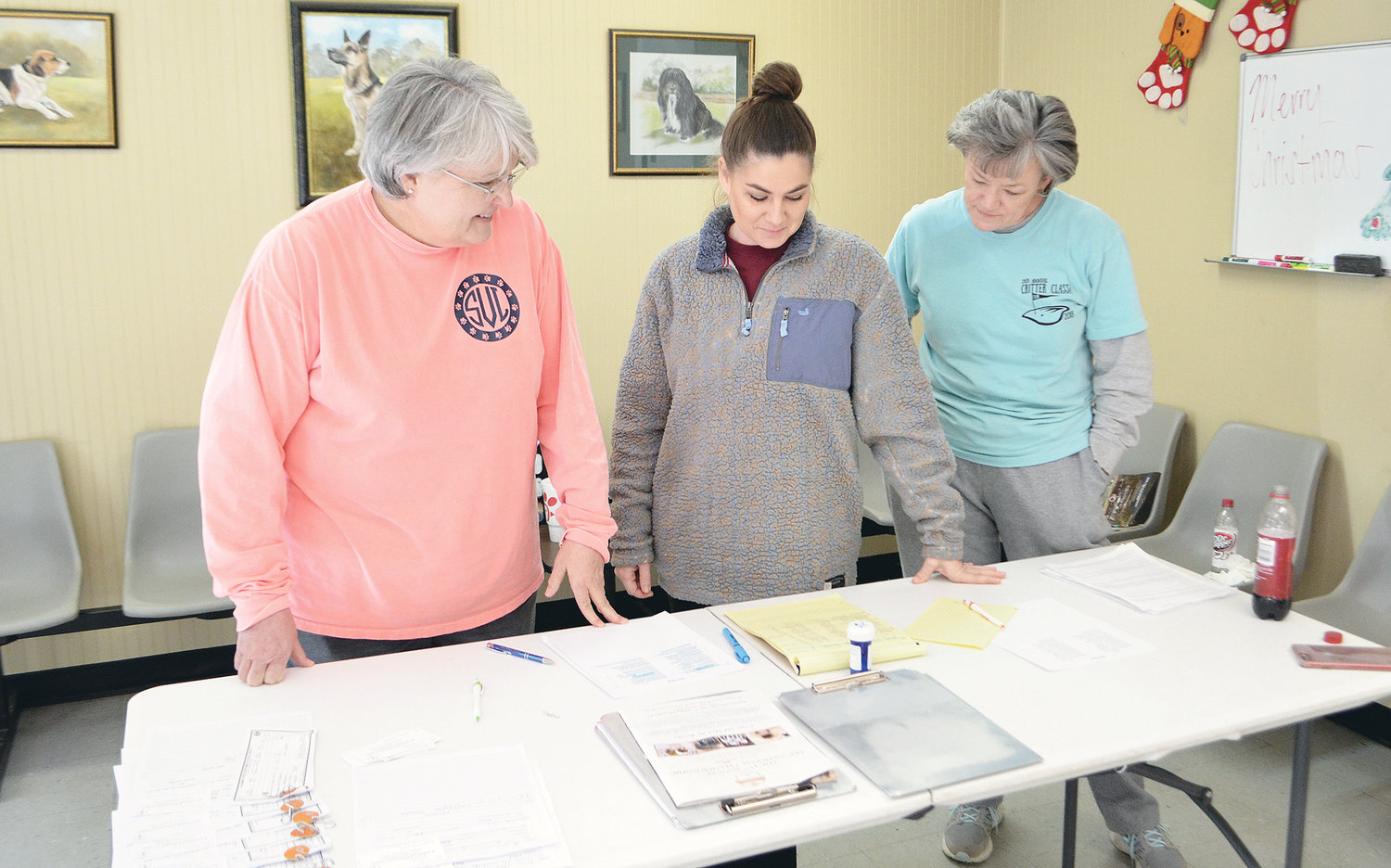 Pictured, from left to right, is Walker County Humane Society Board Director Susie Vann and WCHS board members Amber Stockman and Dee O'Mary going over paperwork for a recent spay and neuter clinic sponsored by the animal rescue organization.