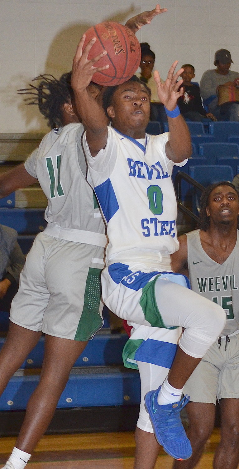 Bevill State's Miguel Williams (0) drives to the goal in front of Enterprise State's Demitri Gallette (11) during Friday's game at Glen Clem Gymnasium. Williams had 29 points in the Bears' 102-94 loss. The loss ended Bevill State's eight-game winning streak.