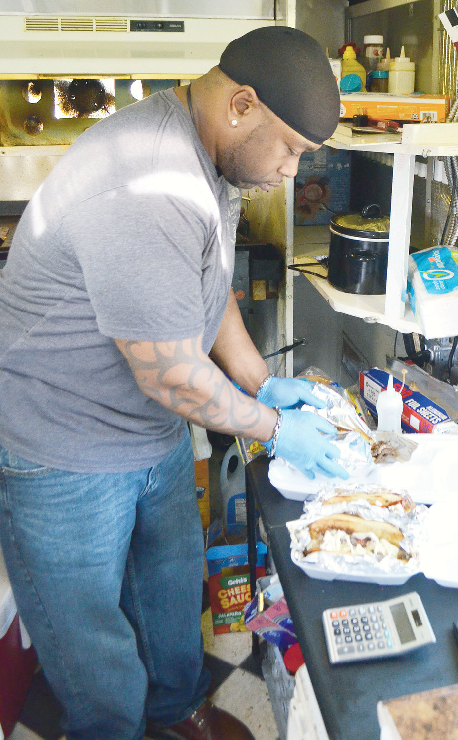Freddy Poe completes a takeout order in his food truck in Jasper Monday.