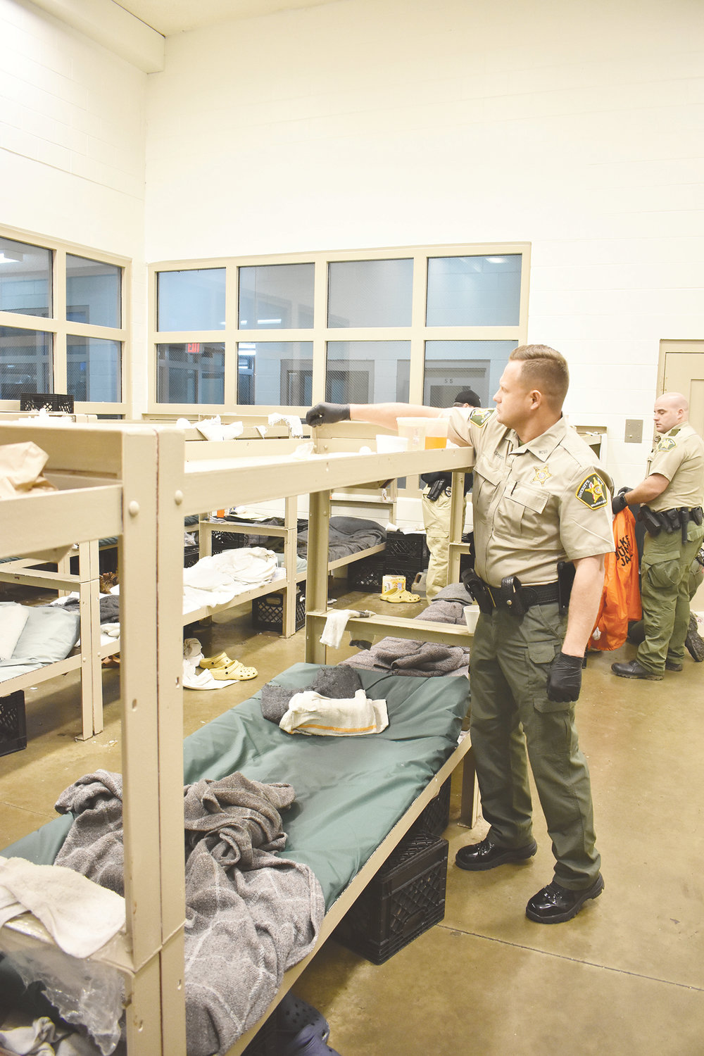 Sheriff Nick Smith reaches over to look for items in the bunks of the trustee area of the Walker County Jail during a sweep held on Wednesday. Smith is eager to address a number of issues at the jail, and has been seen often in the cell areas this week.